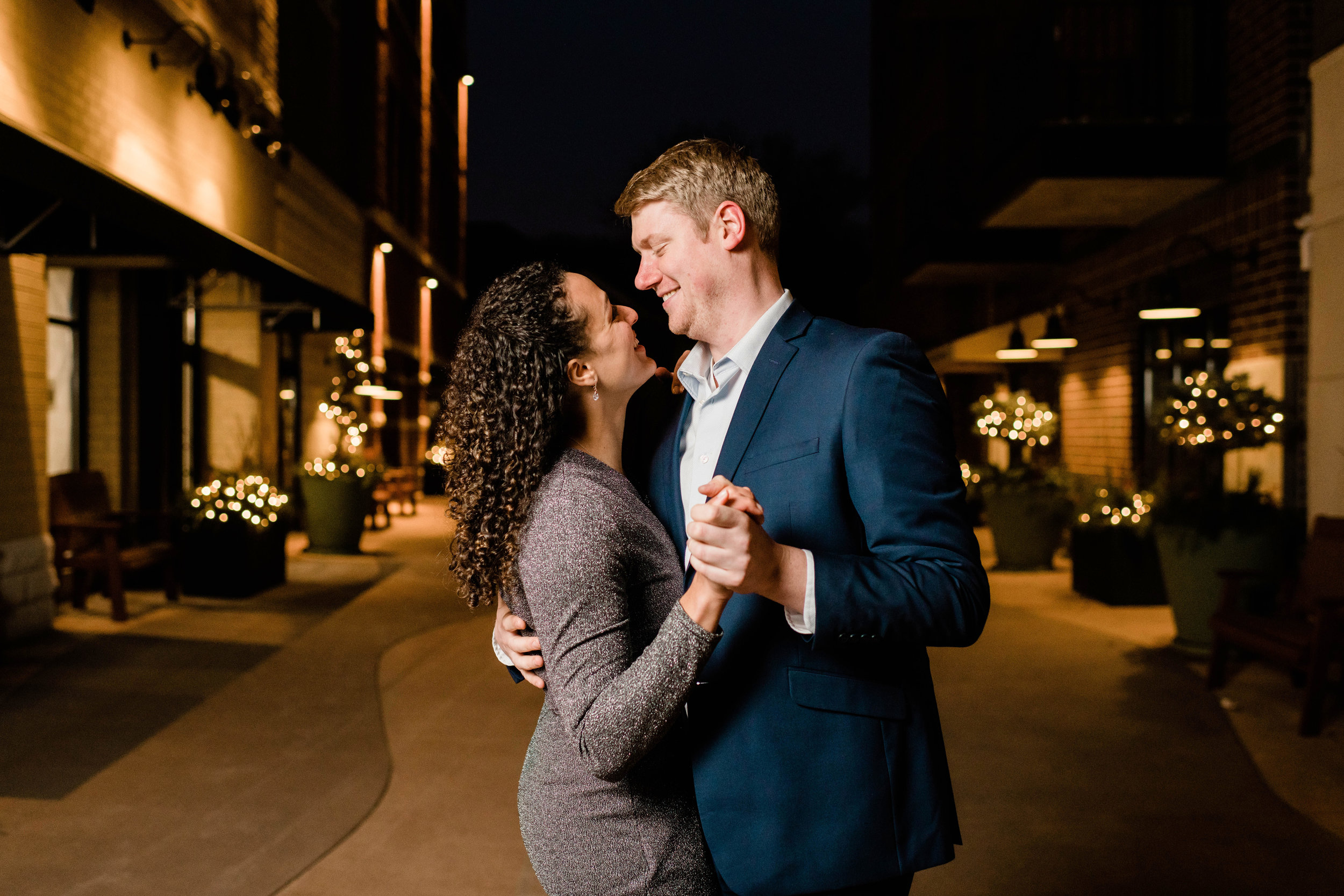 Engaged couple dancing in the streetlights