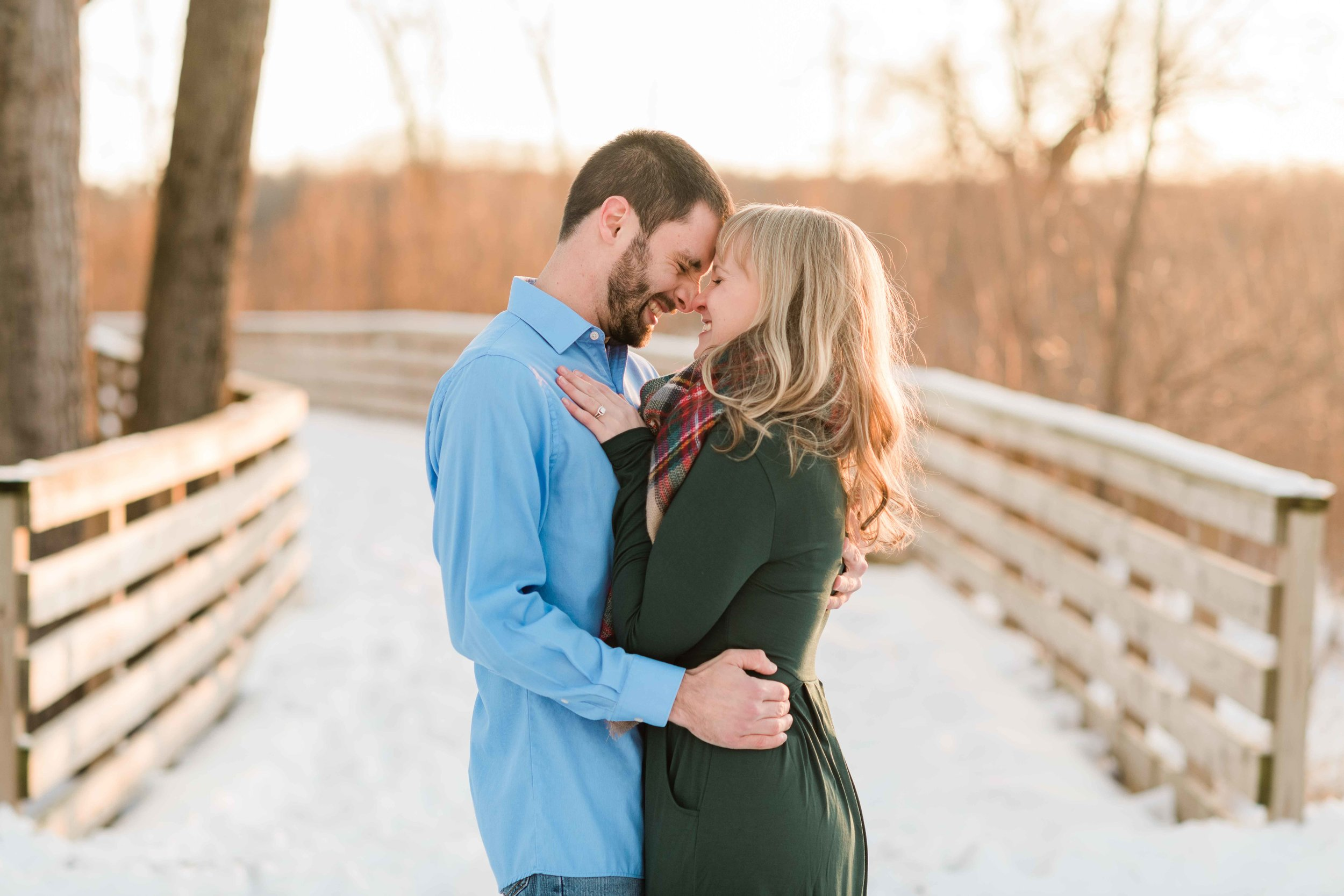 Engaged couple stands forehead to forehead