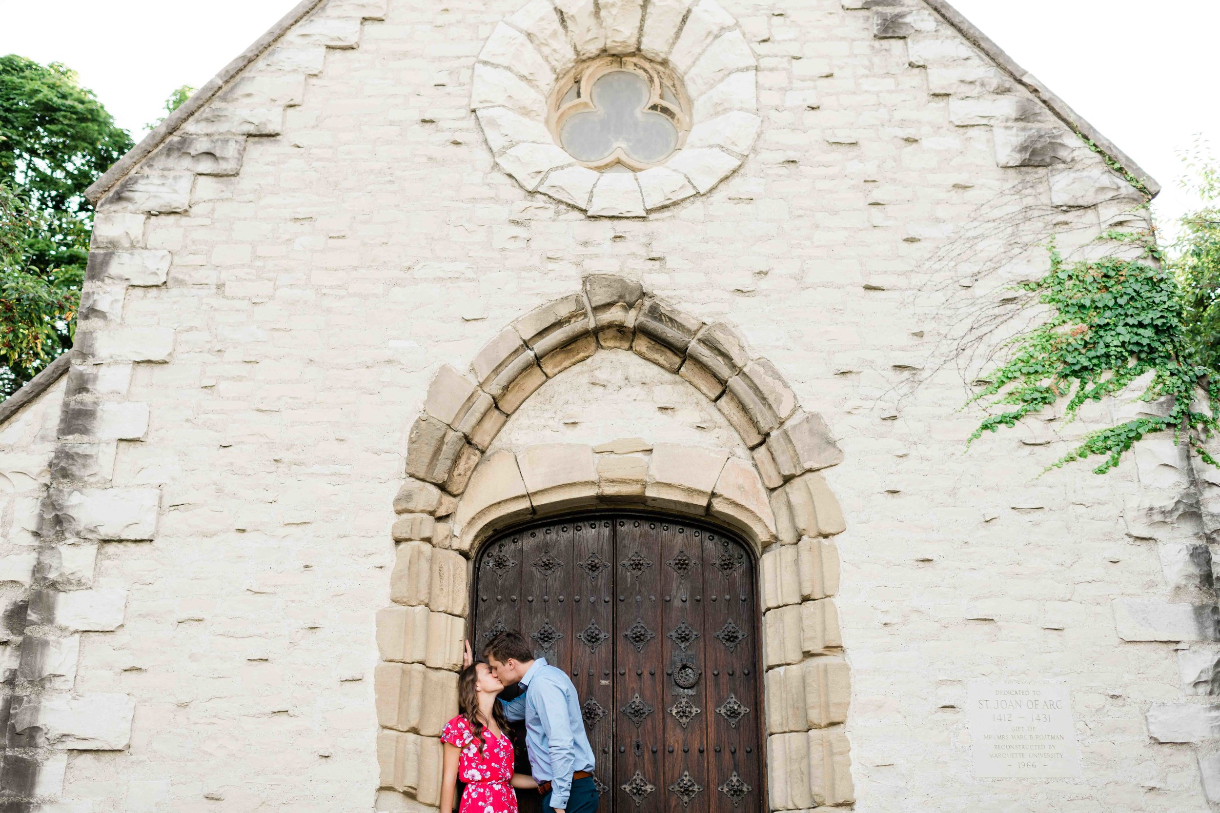Engaged couple kissing in front of a garden house