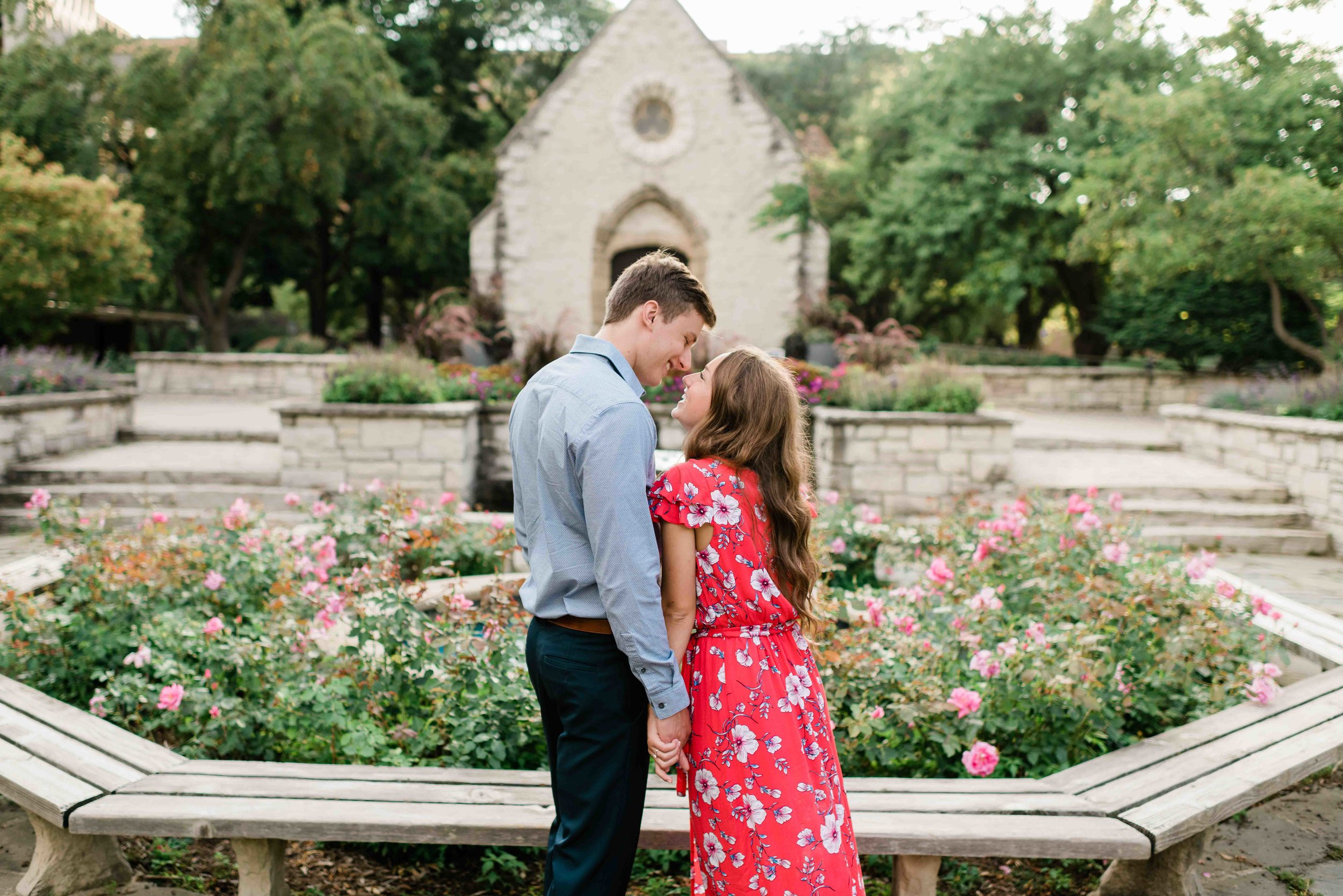 Engaged couple kissing in a garden