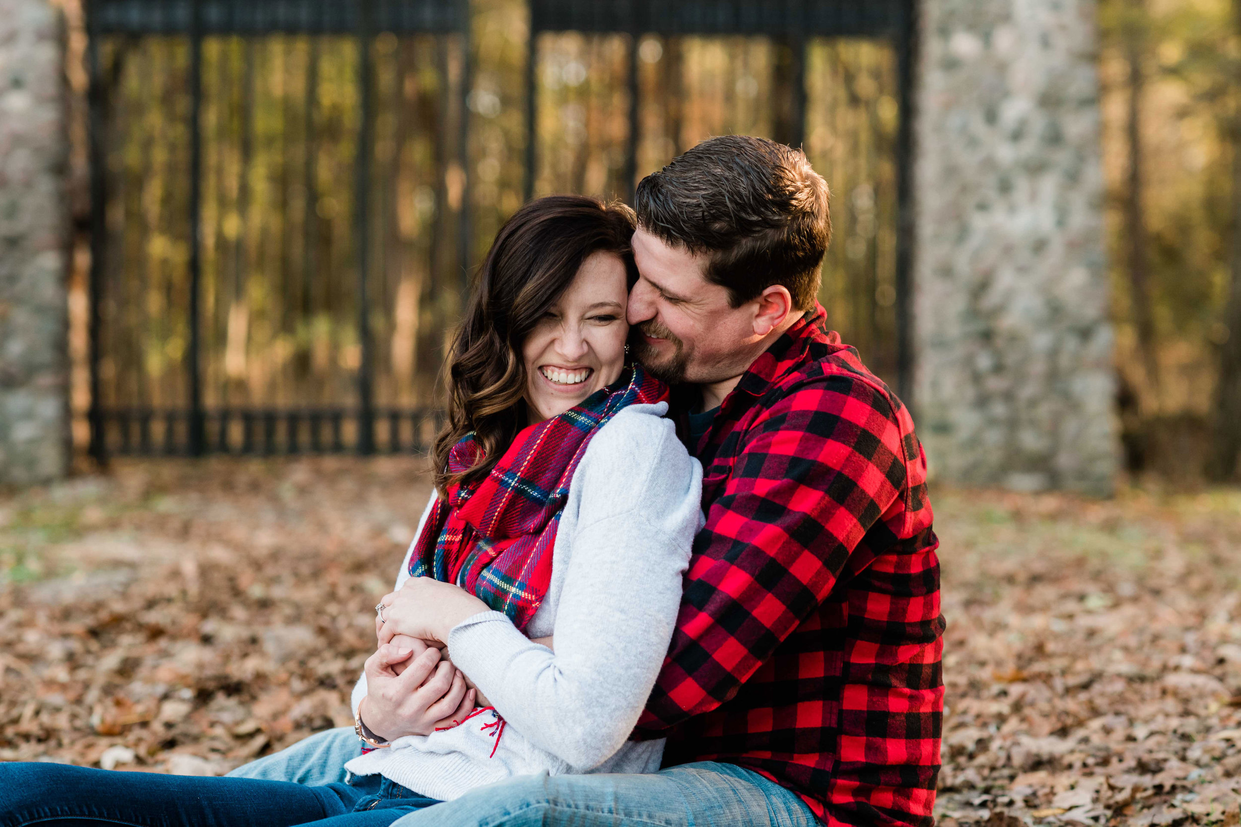 Engaged couple snuggling in the leaves outside