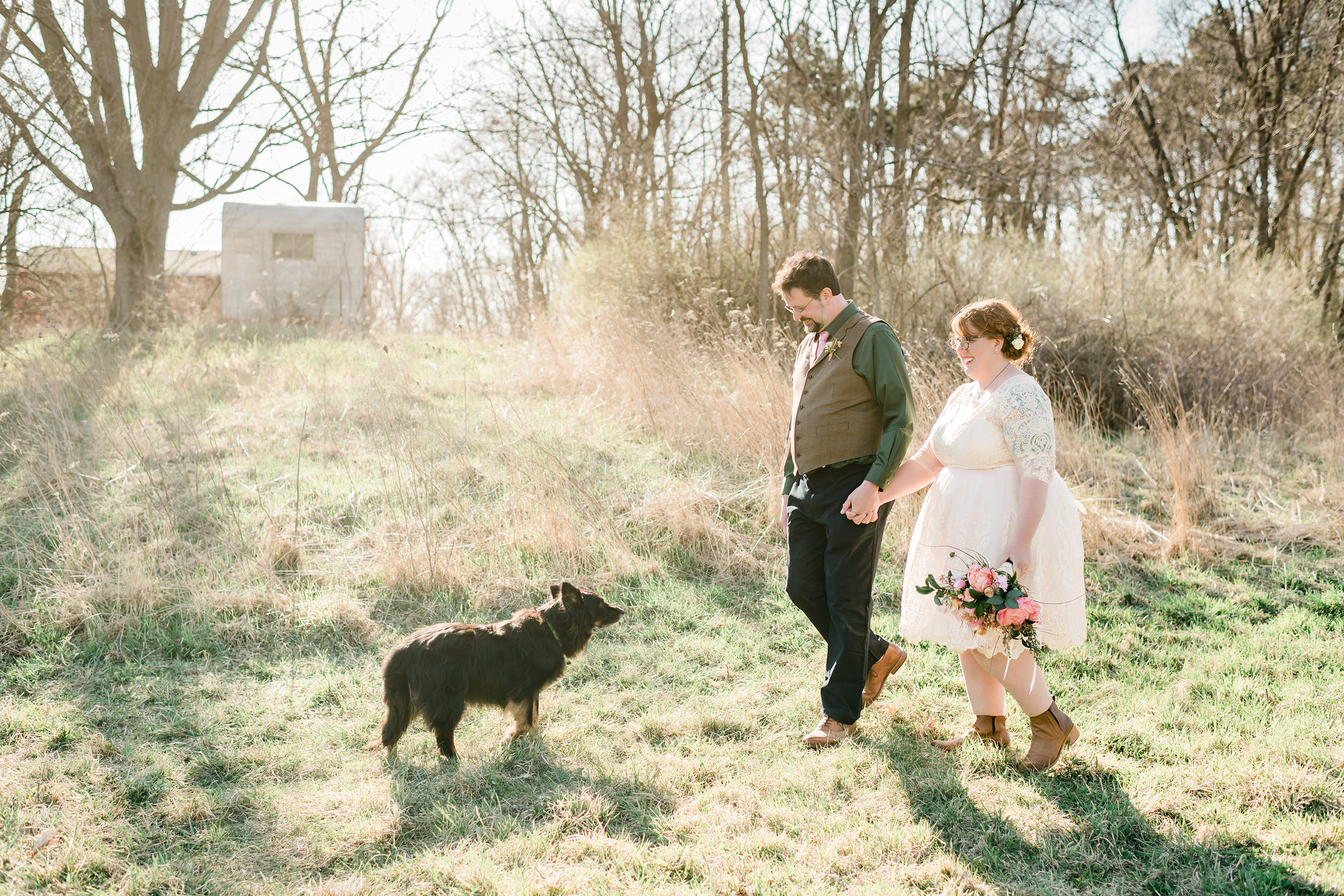 Bride and groom walking with their dog