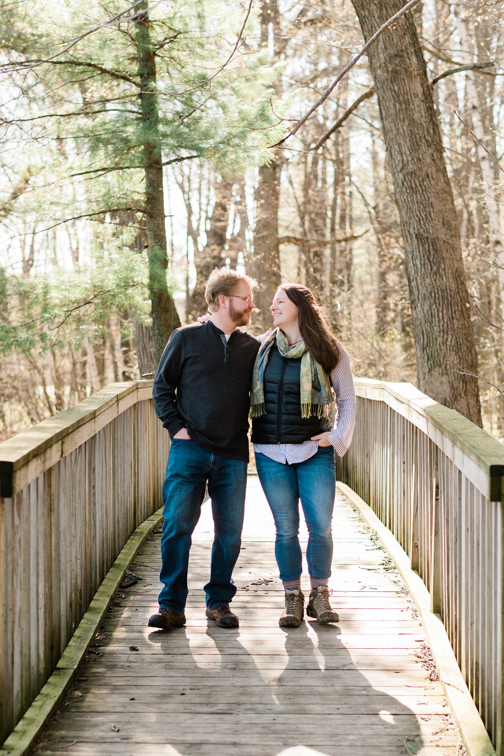 Engaged couple walking on a bridge
