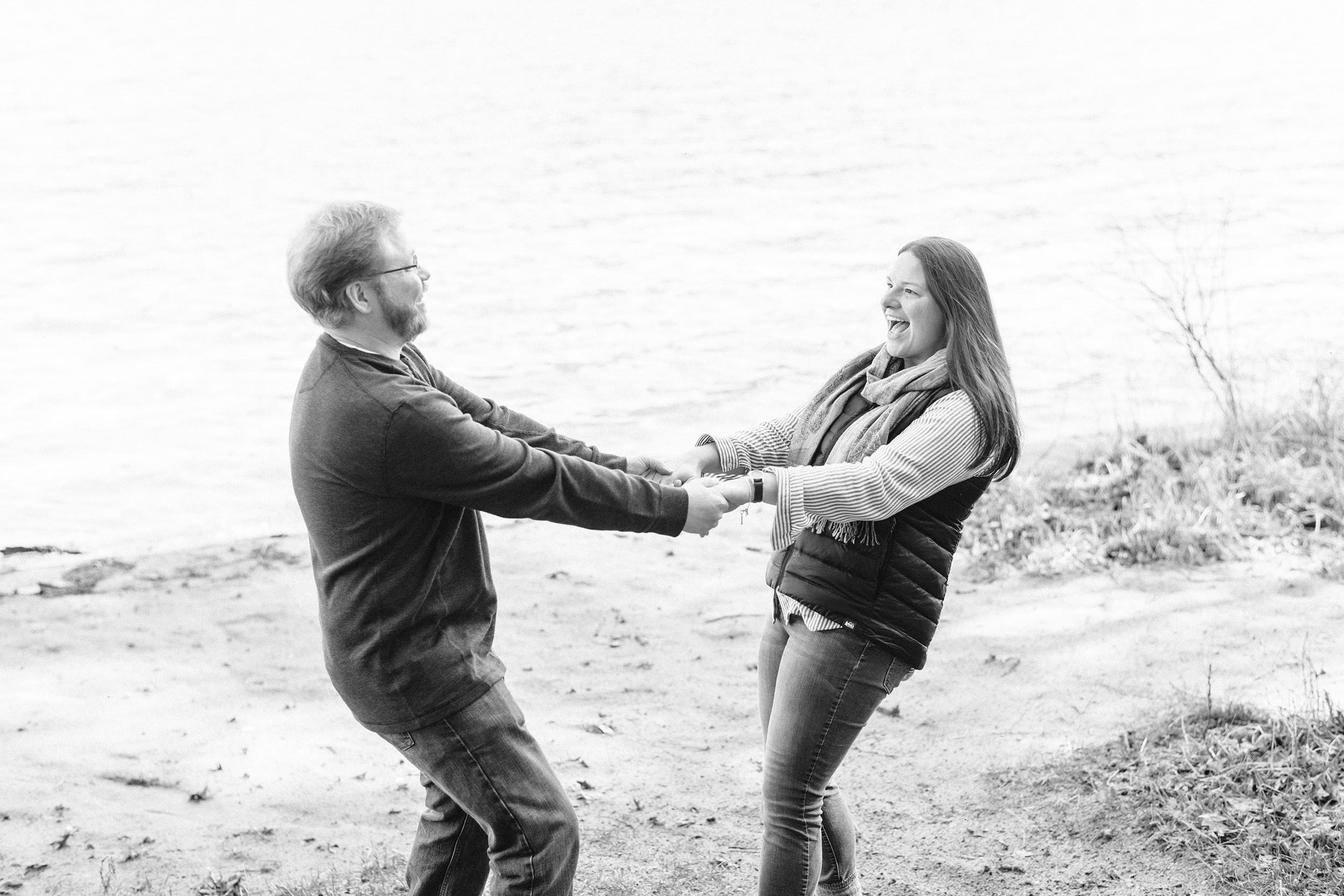 Engaged couple swinging each other around