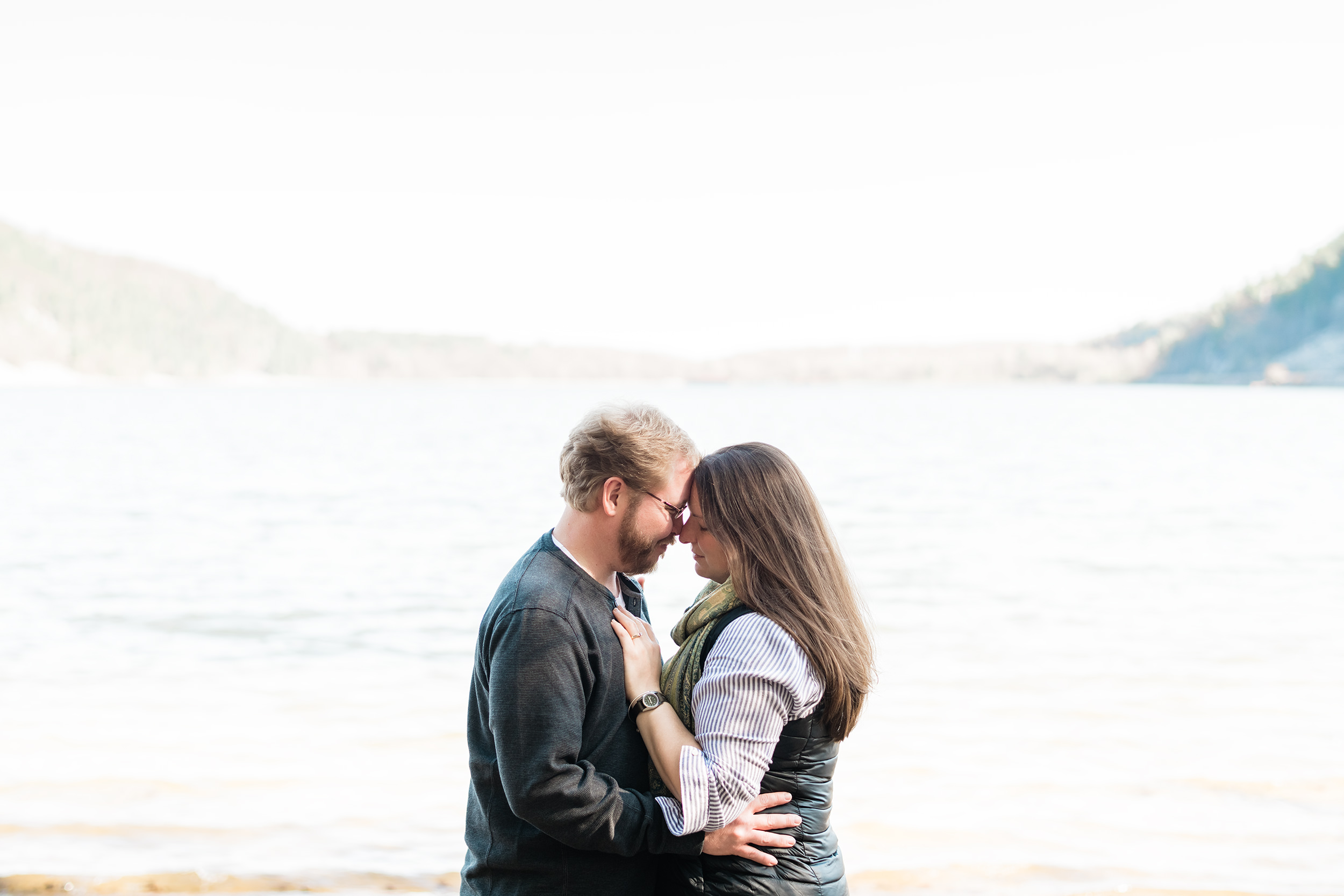 Engaged couple forehead to forehead in front of Devil's Lake