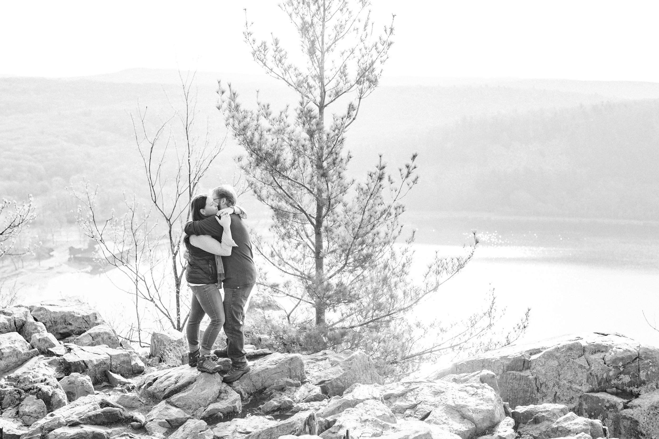 Engaged couple hugging at the peak of Devil's Lake State Park
