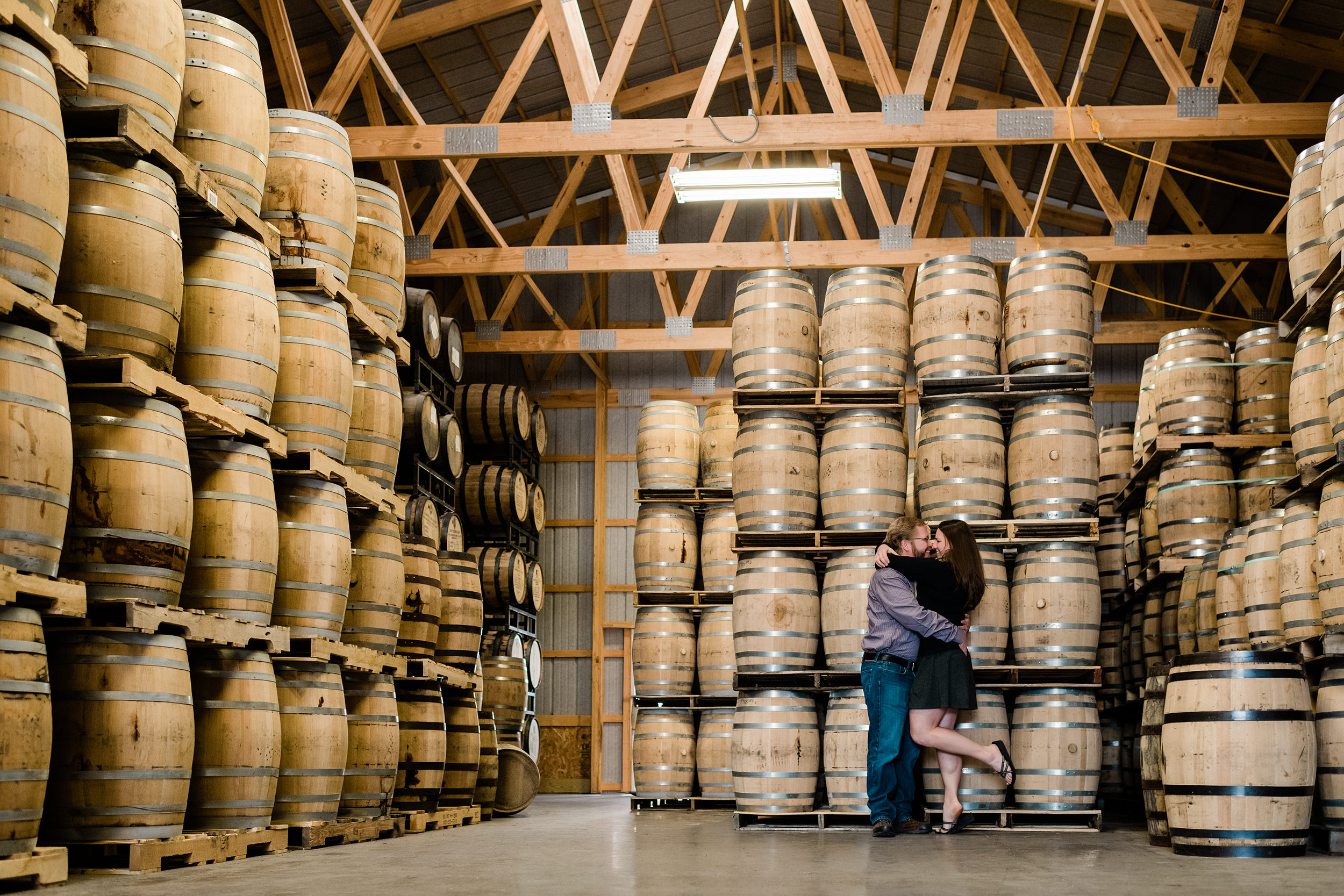 Engaged couple in the rickhouse at Driftless Glen Distillery