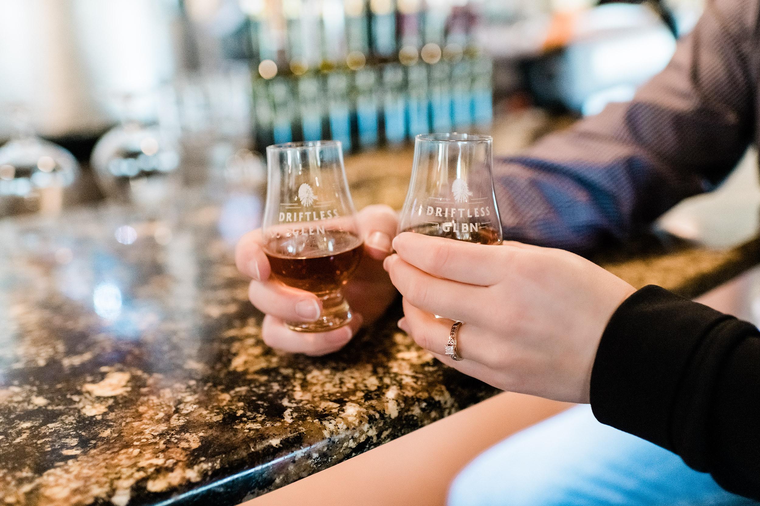 Engaged couple drinking bourbon at Driftless Glen Distillery in Baraboo