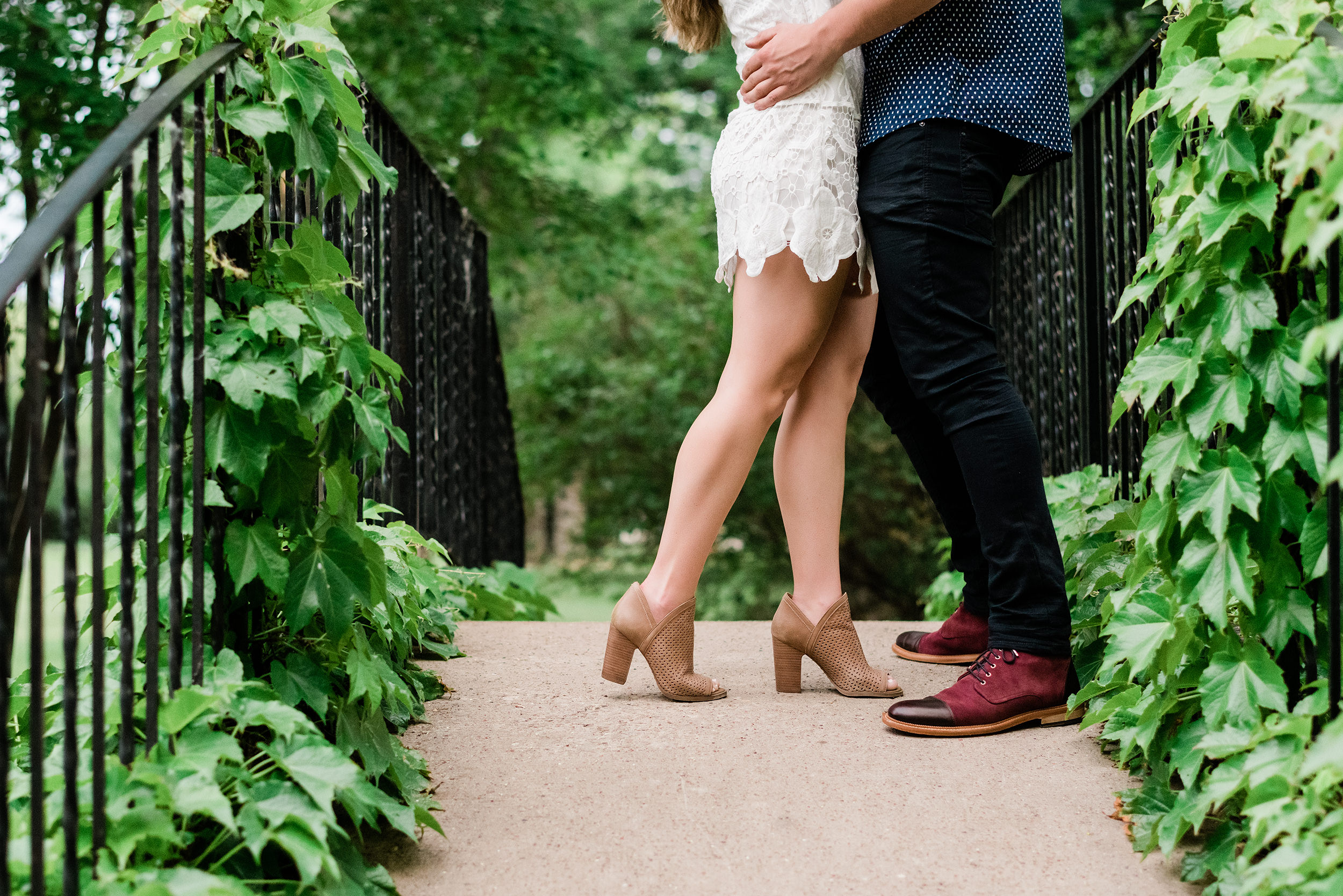 Engaged couple on a bridge showing off their shoes