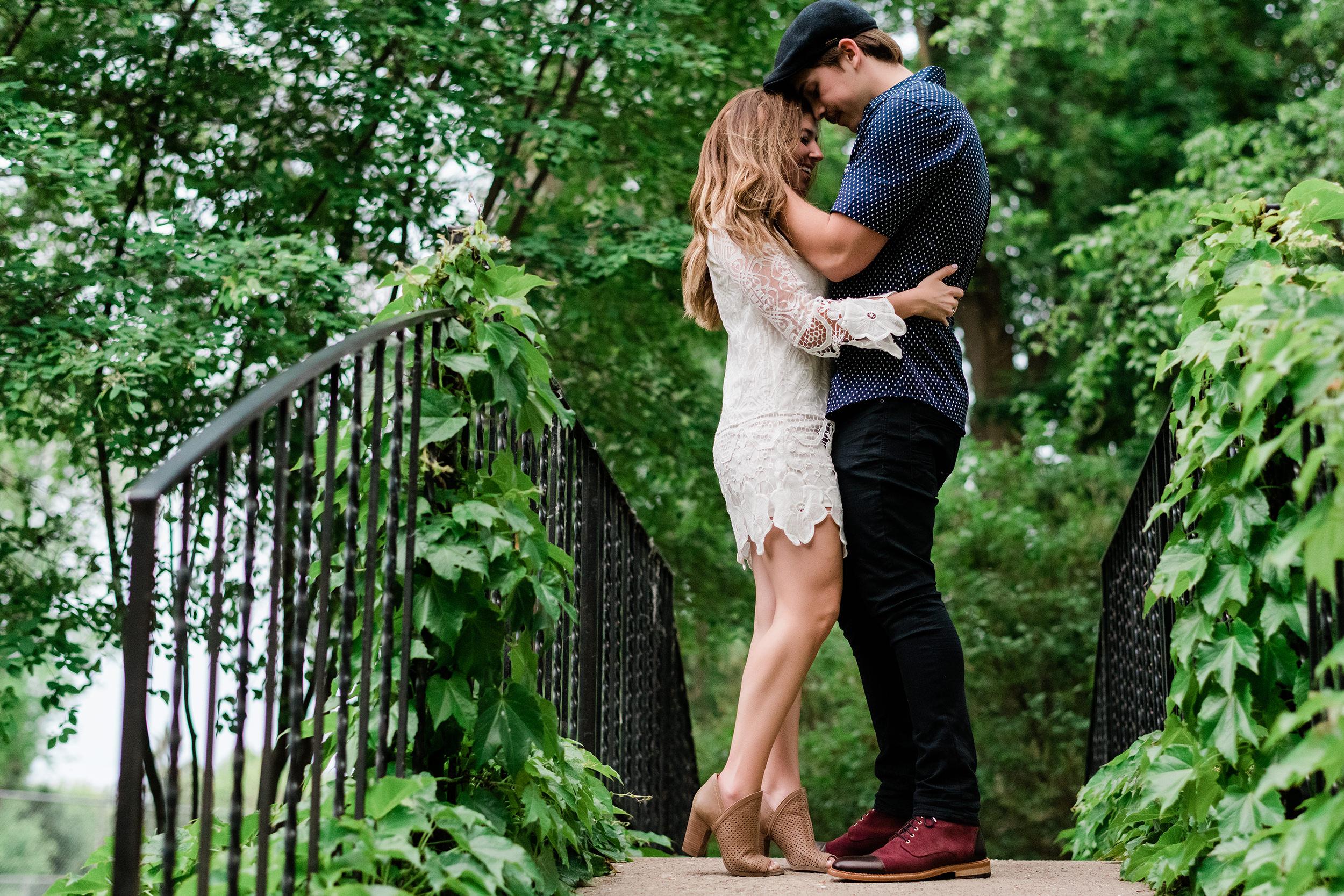 Man runs his fingers through his fiancé's hair as they stand on a bridge