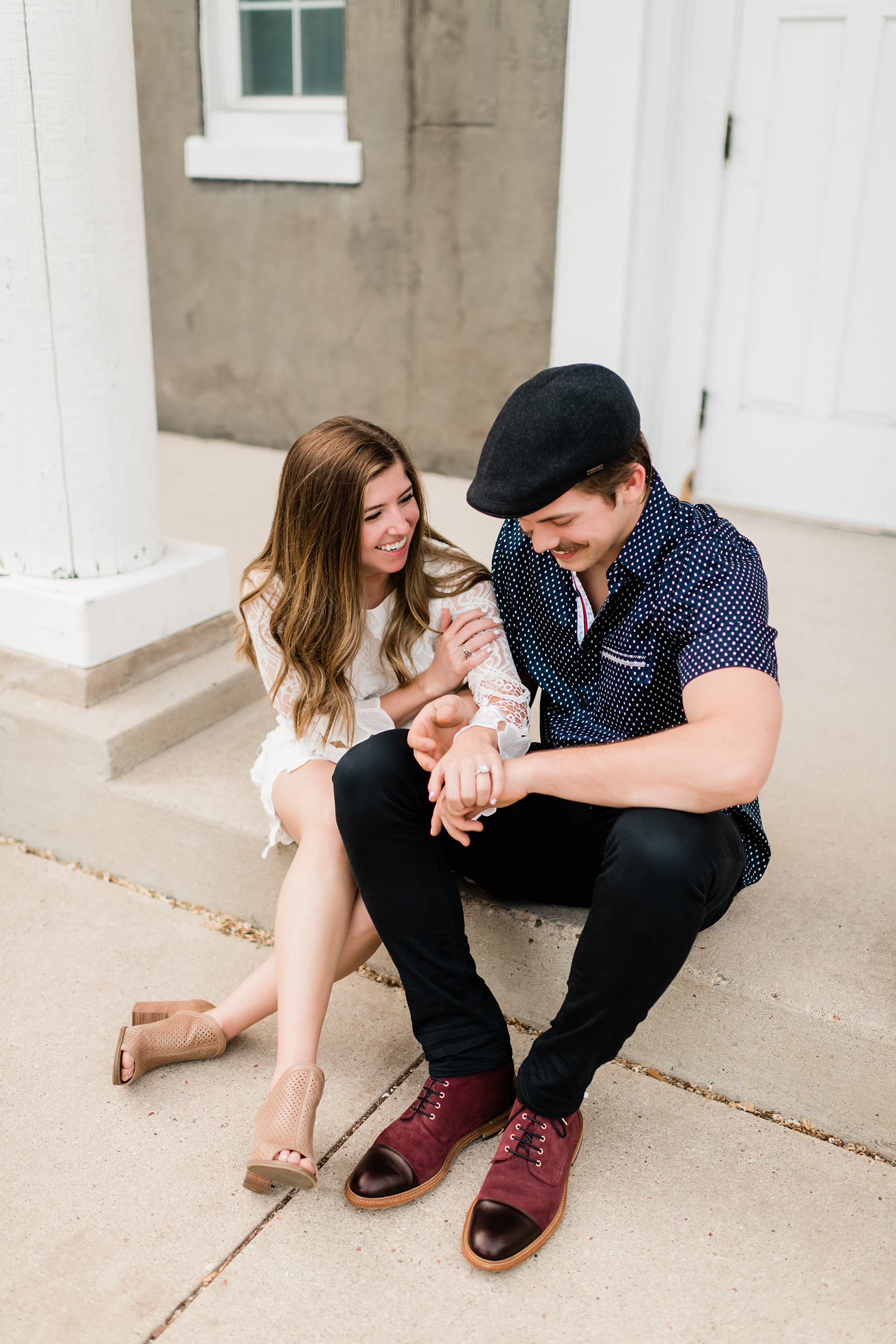 Engaged couple cuddling on a front porch