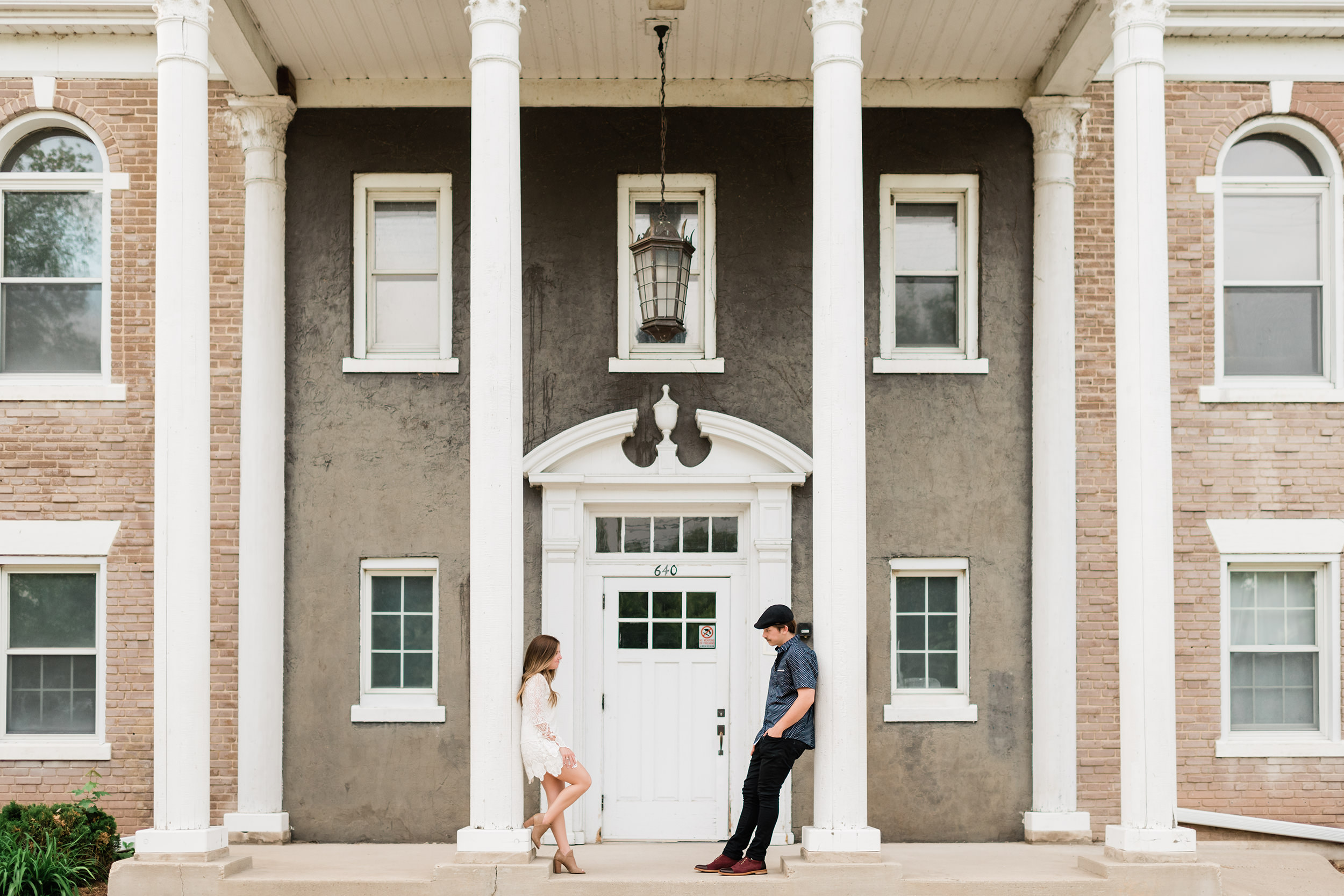 Engaged couple leaning against white pillars