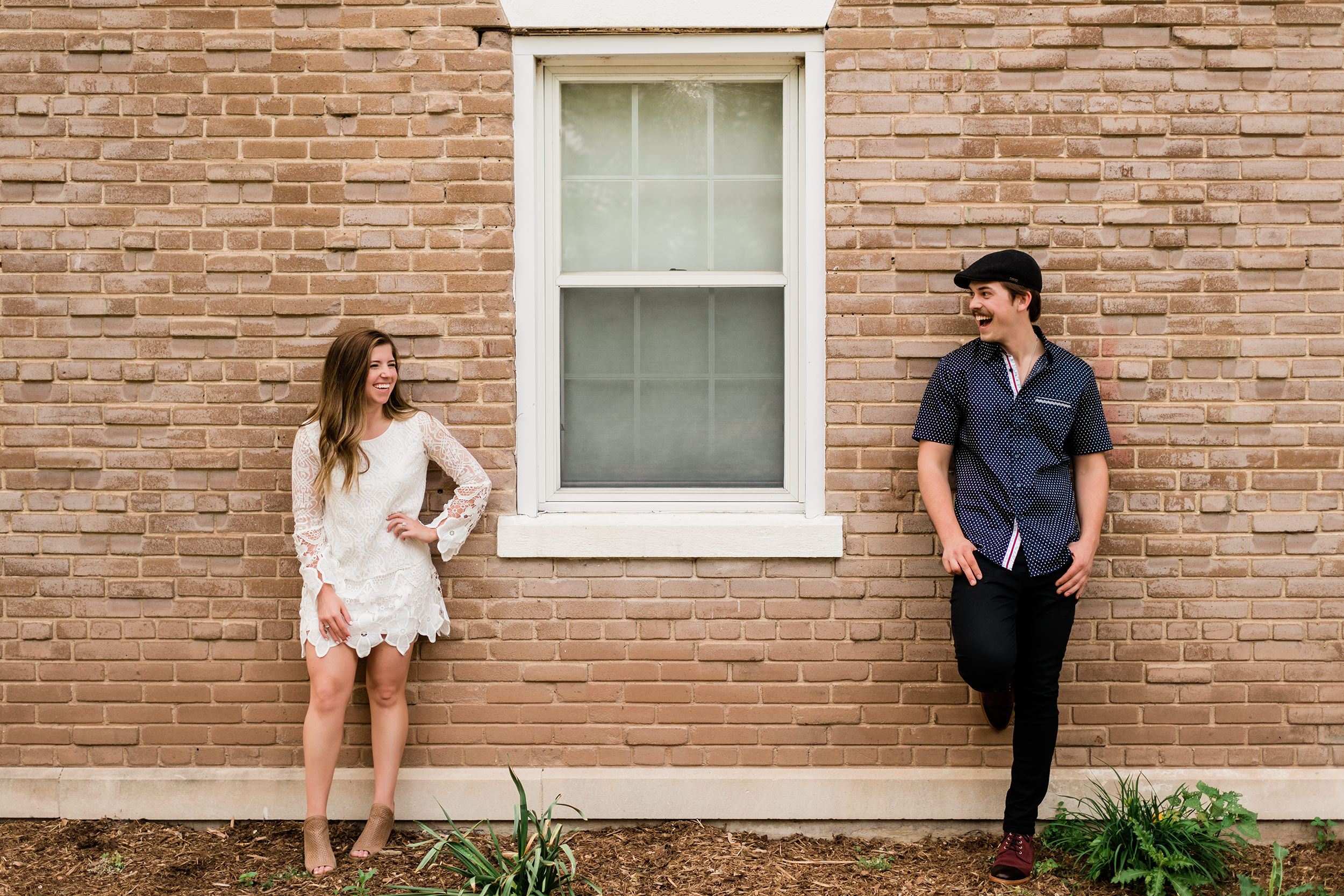 Engaged couple leaning up against a brick building and looking at each other