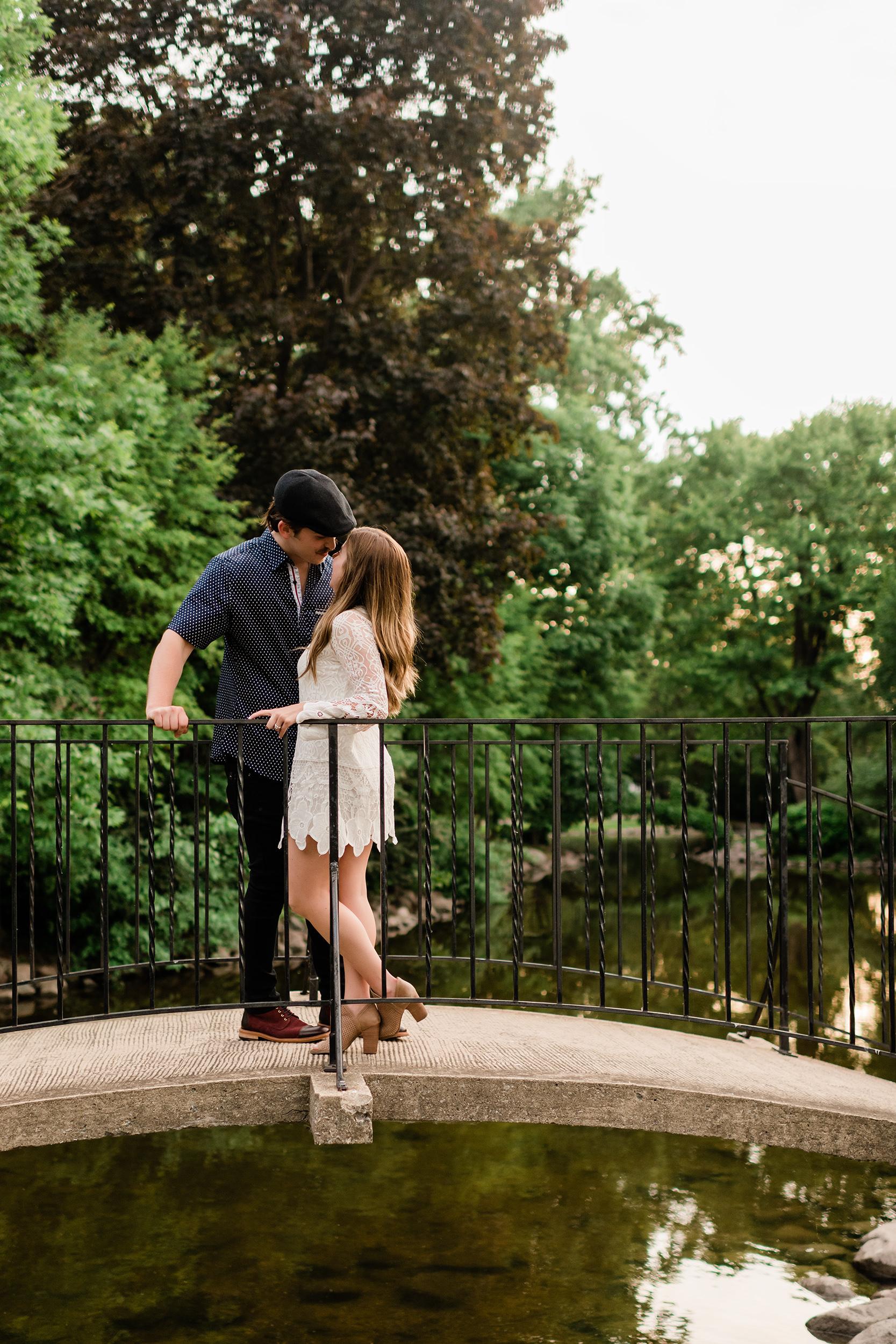 Engaged couple kissing on a bridge