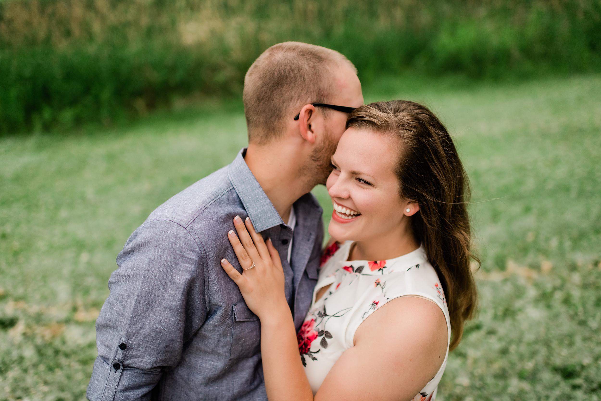 Man whispering in his fiancé's ear