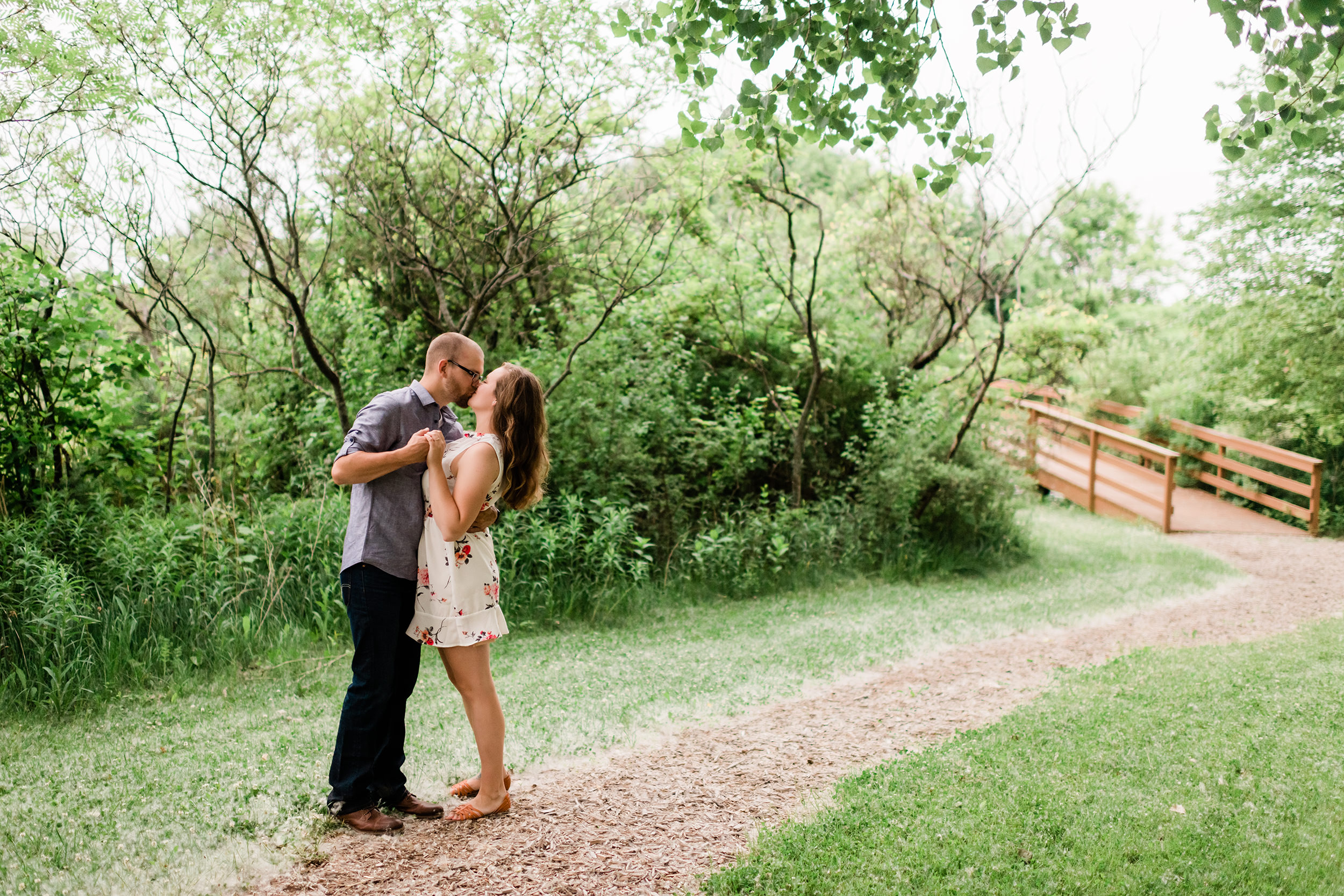 Engaged couple kissing by a bridge