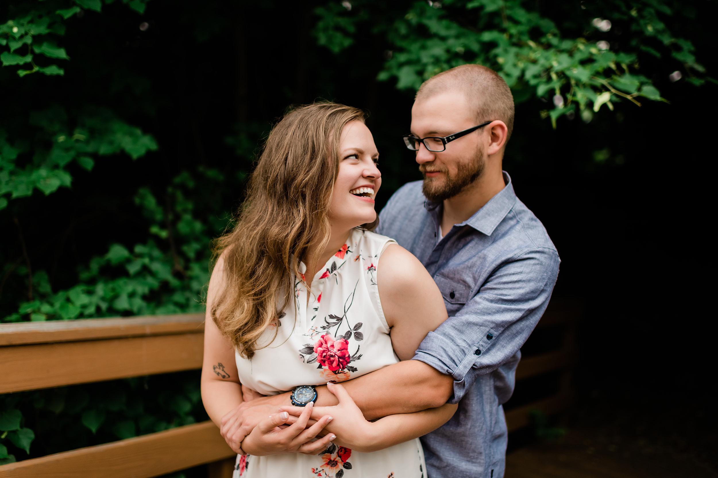 Man wraps his arms around his fiancé