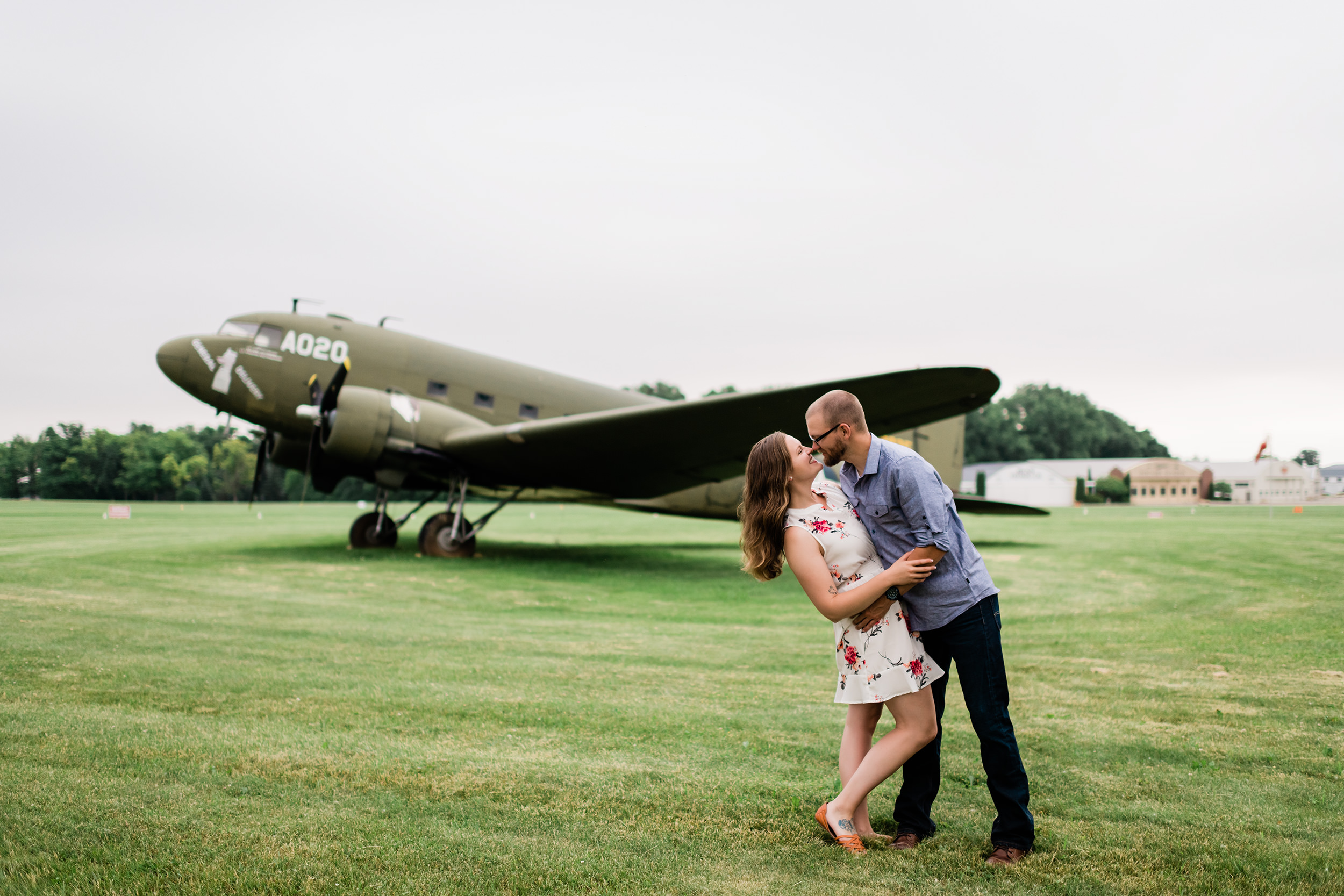 Engaged couple kissing in front of an airplane