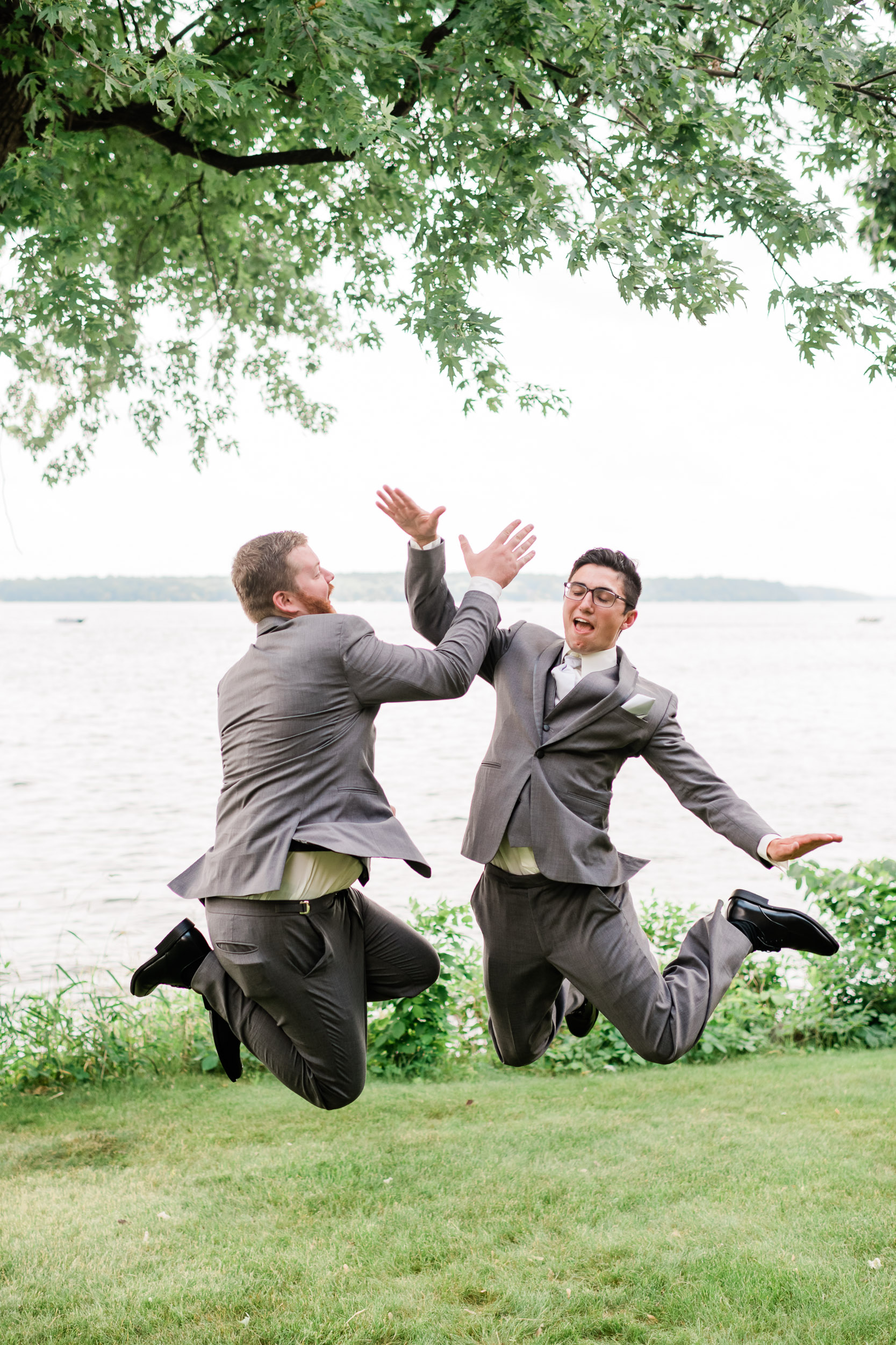 Groomsman and groom jump and high five each other