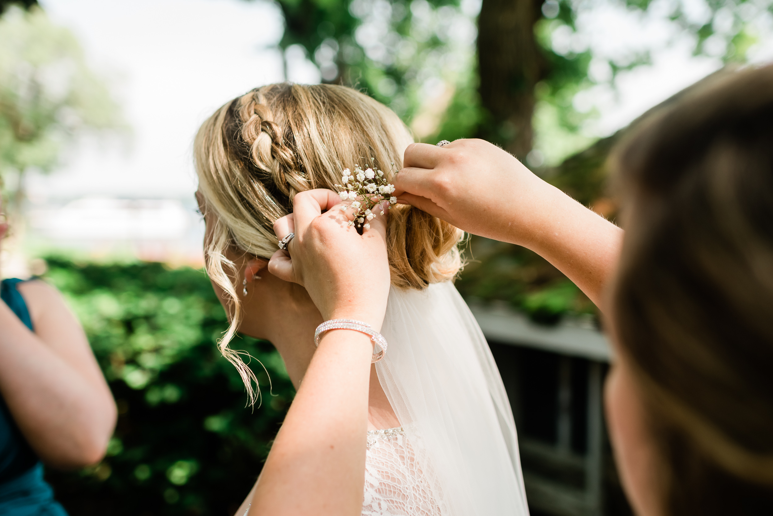 Bridesmaid puts baby's breath in bride's hair