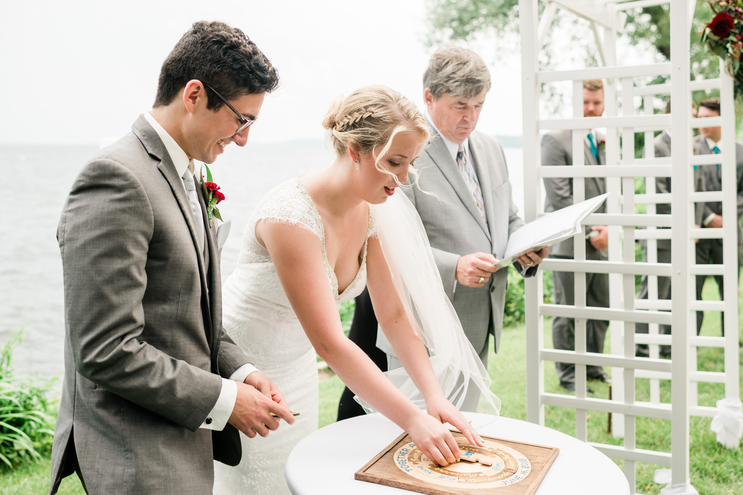 Bride and groom putting a piece in their unity puzzle