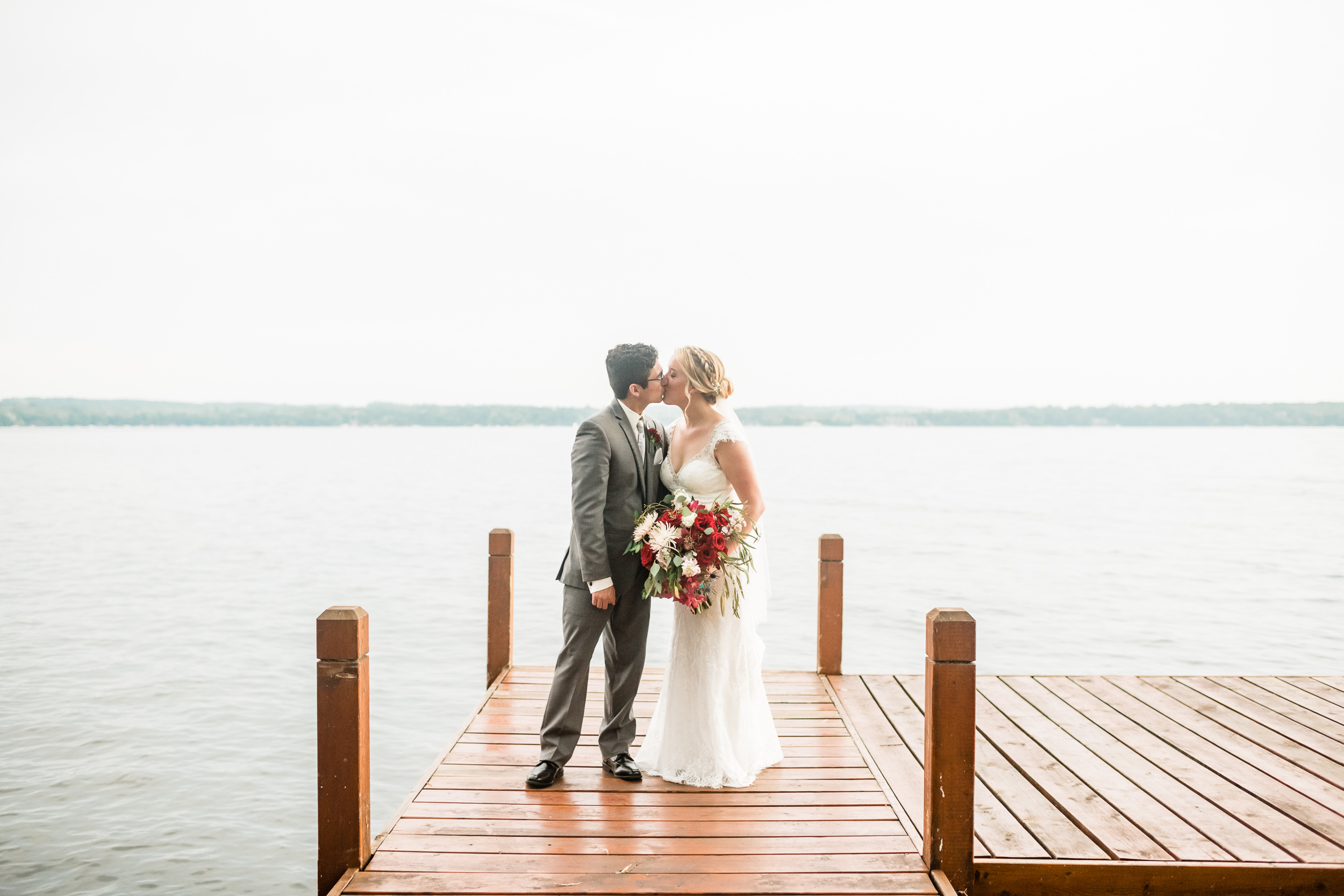 Bride and groom kissing on a dock