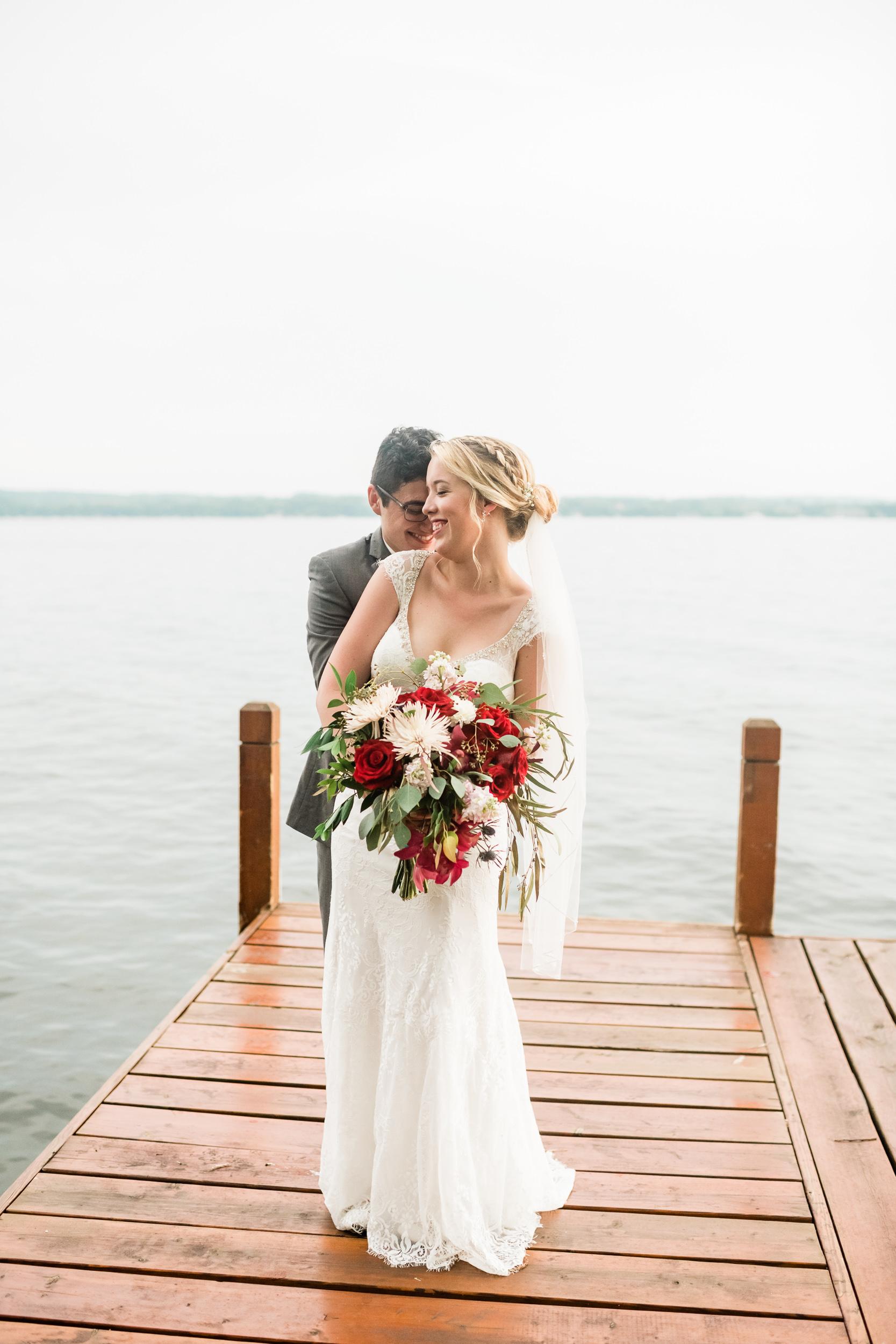 Groom hugging bride from behind on a dock