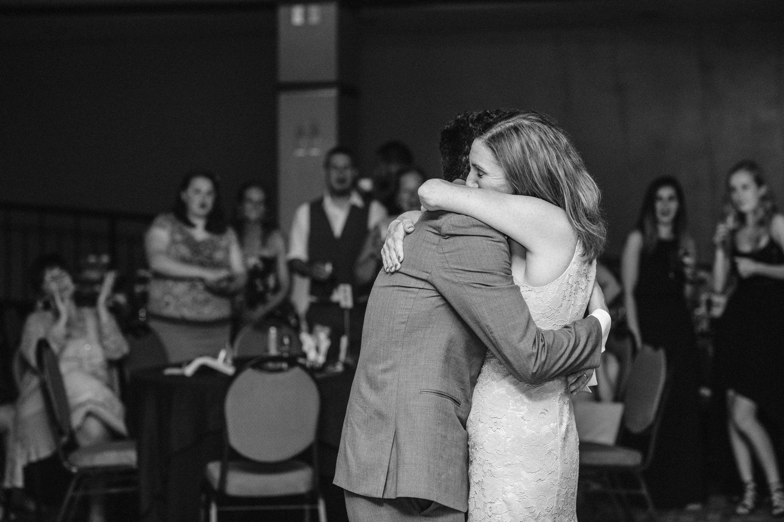 Groom hugging his mother during their first dance