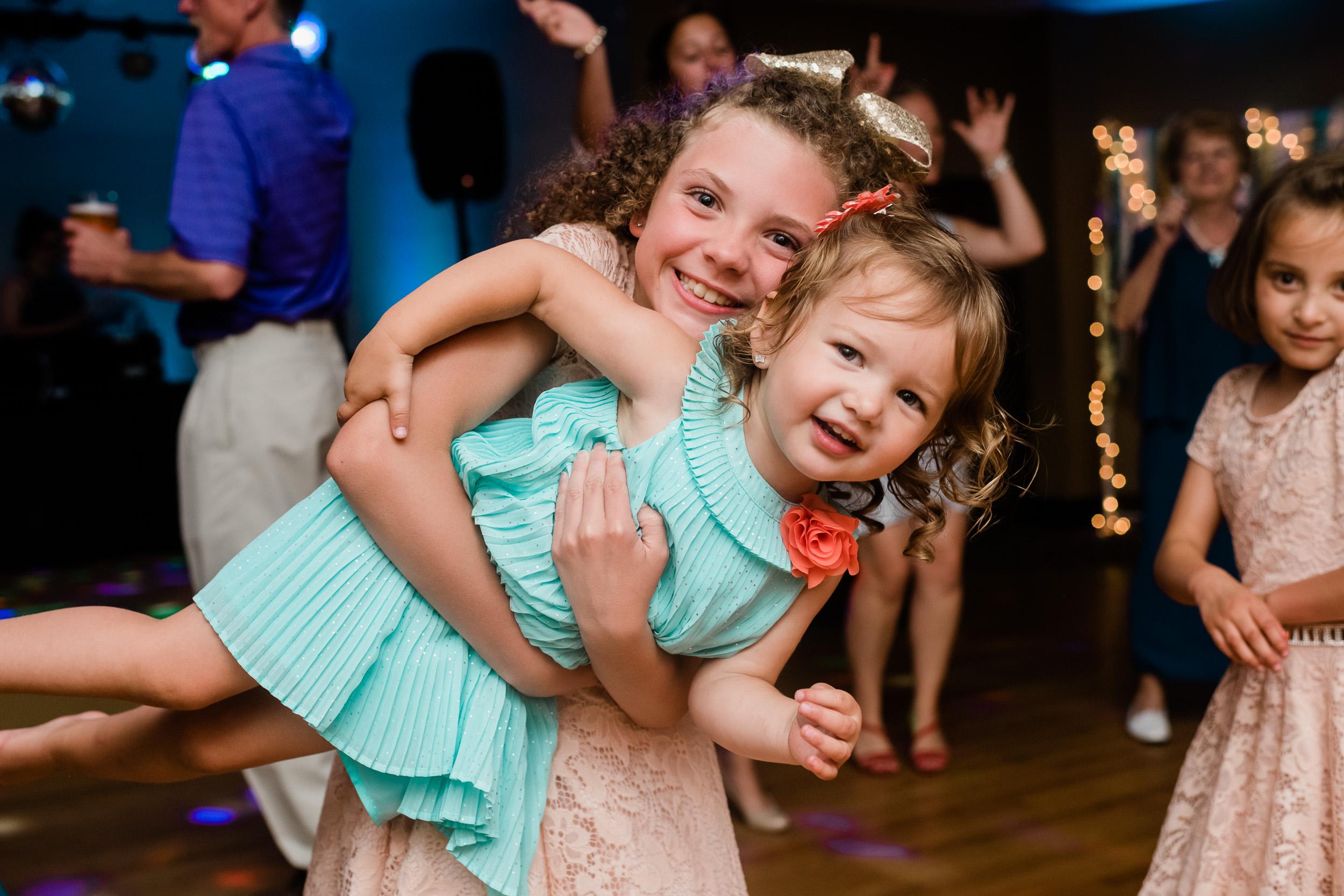 Girl holds little girl on the dance floor