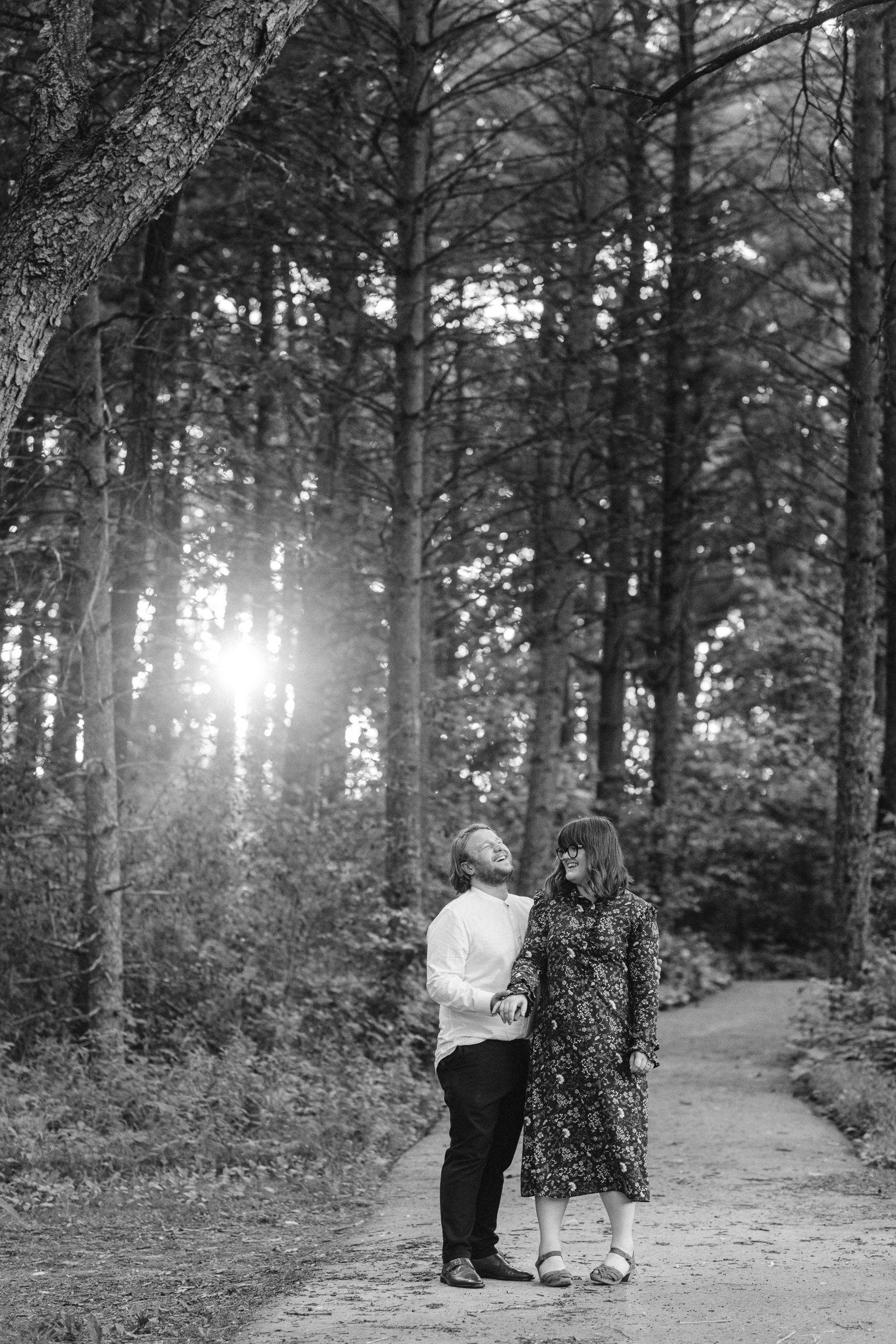 Engaged couple laughing in the woods