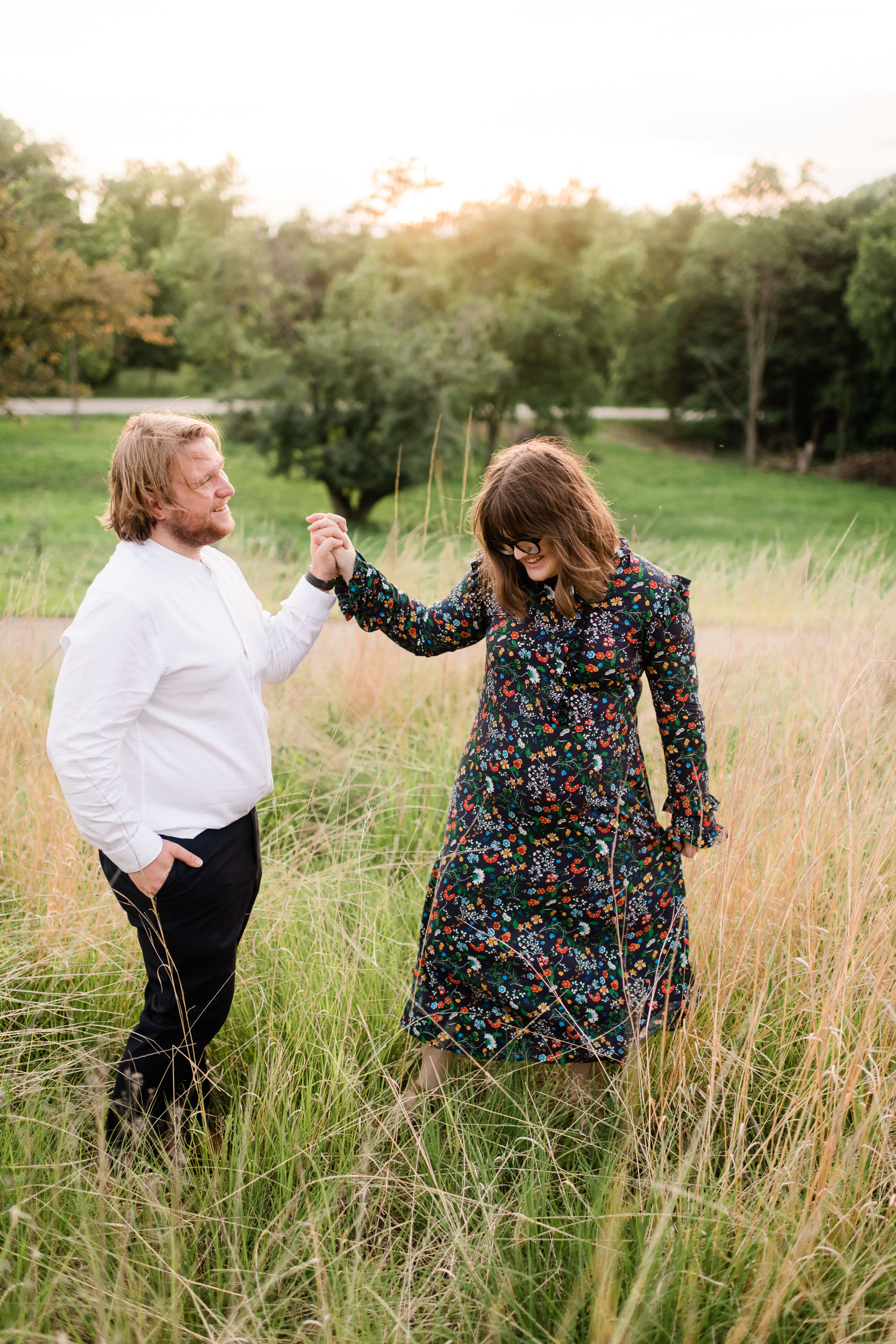 Engaged couple twirling in a field