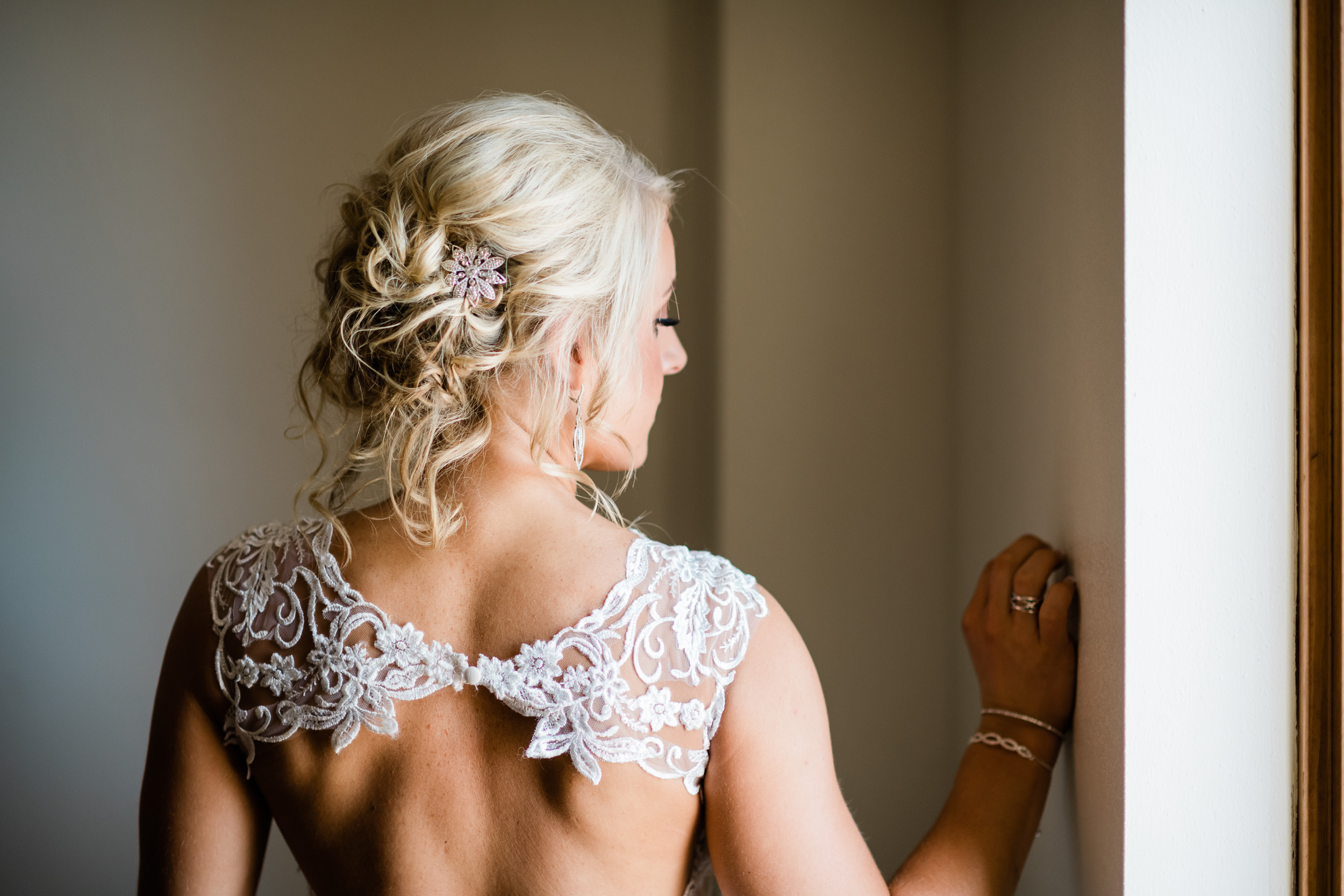 Back of bride's dress as she looks out the window
