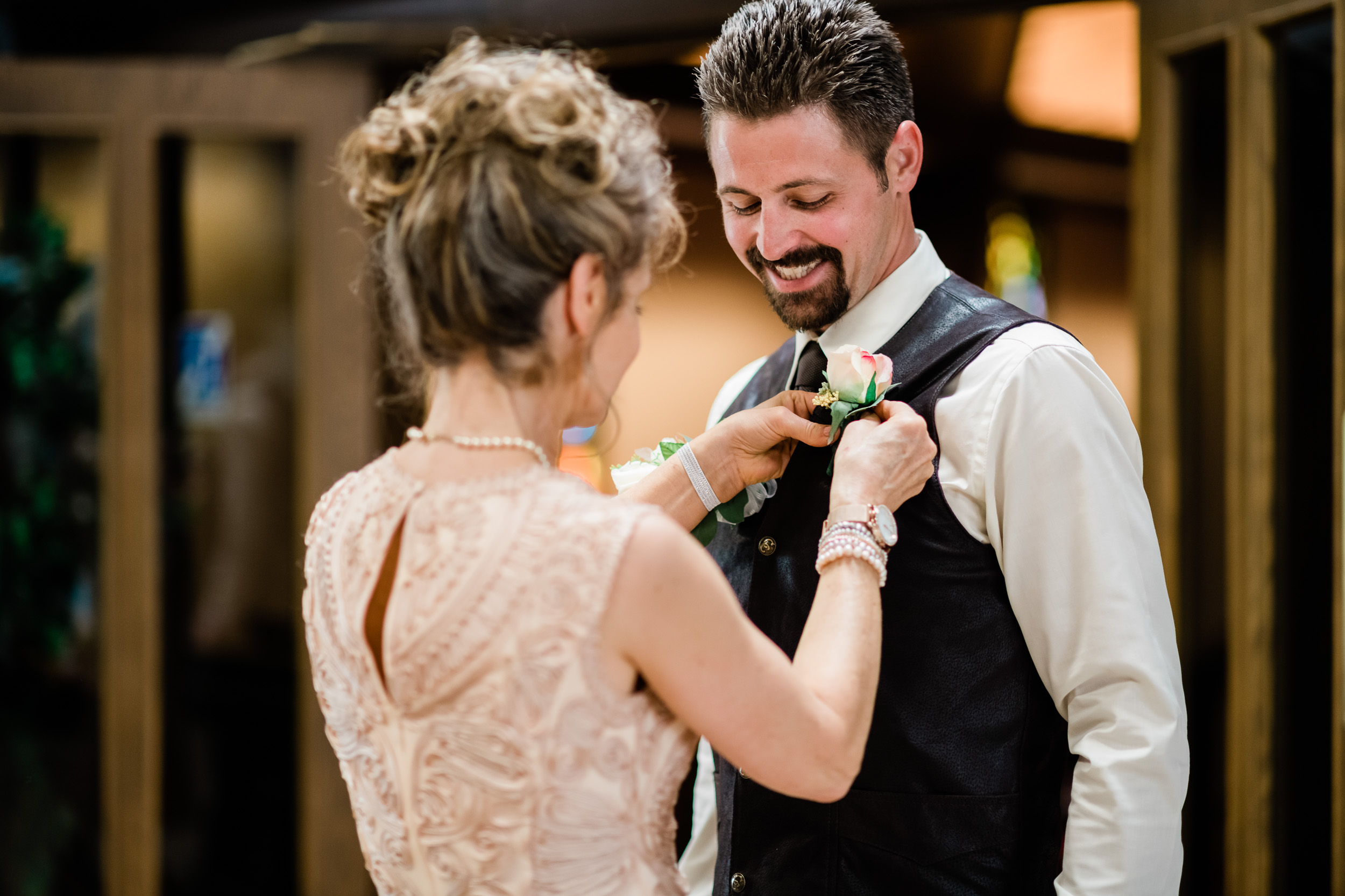 Mother of groom pinning on his boutonnière