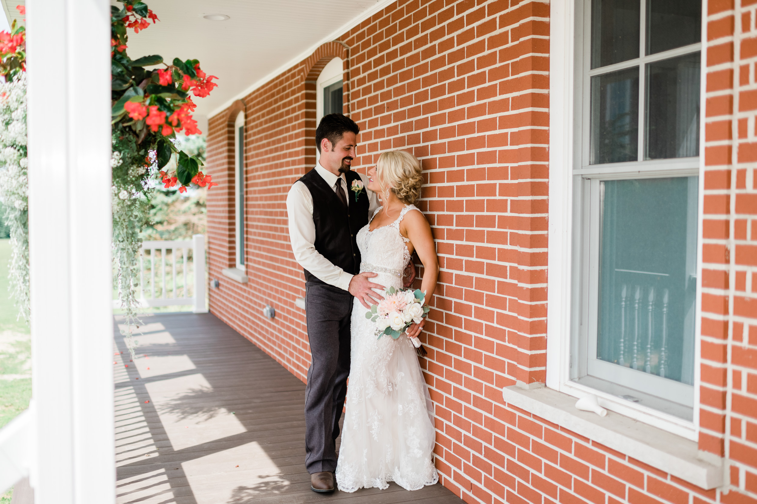 Bride and groom looking at each other on front porch