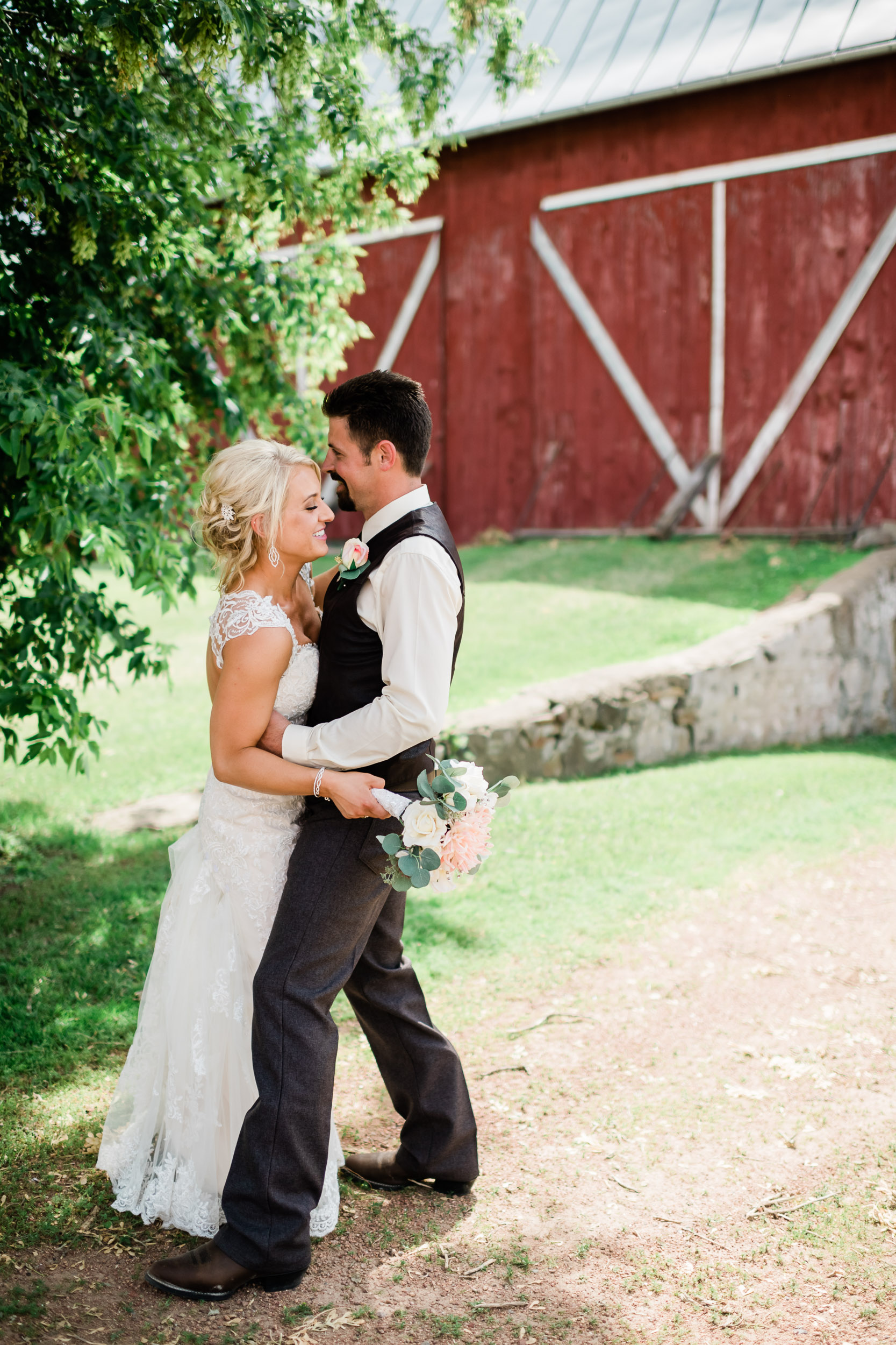 Bride and groom slow dancing in front of barn