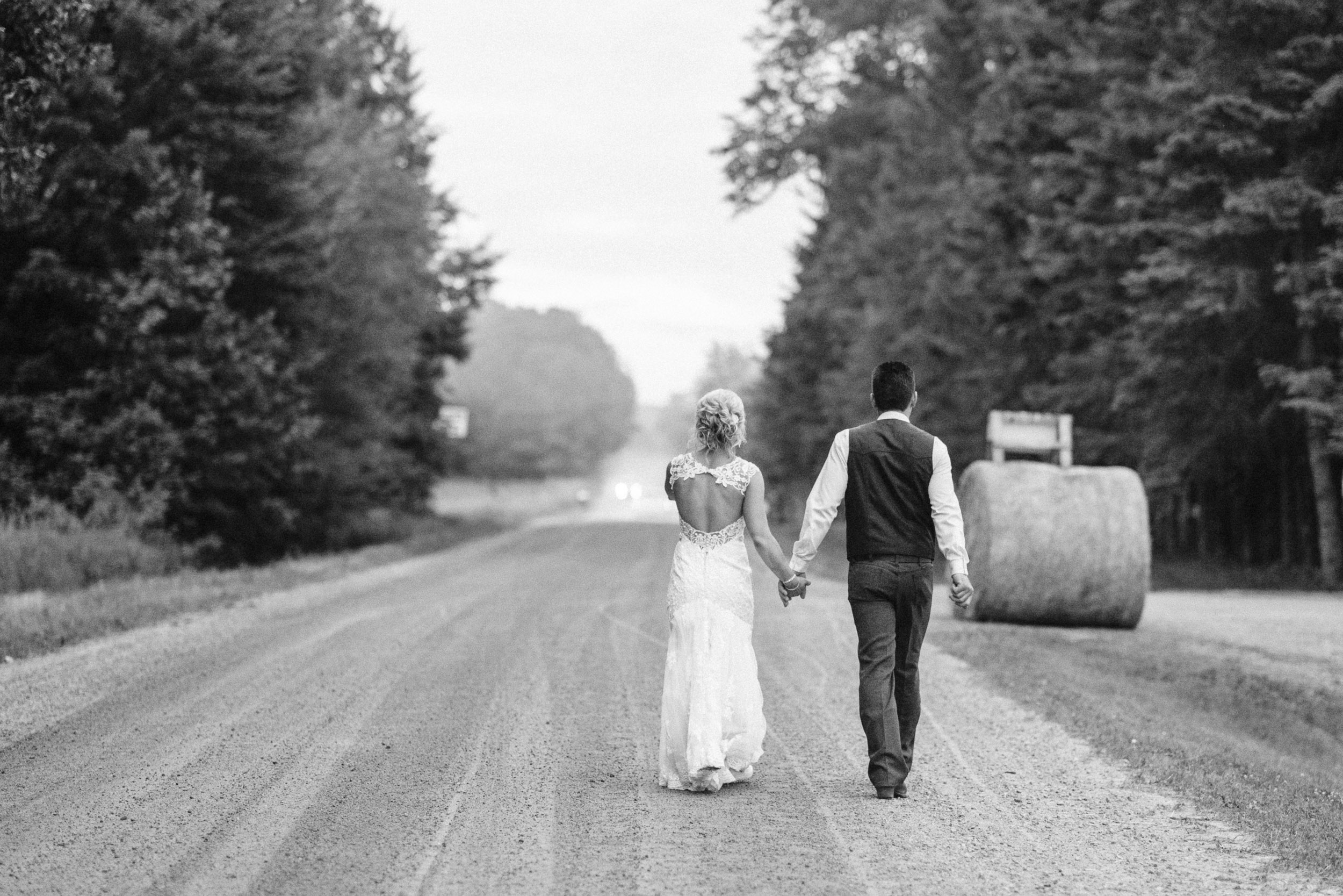 Bride and groom walking down gravel road
