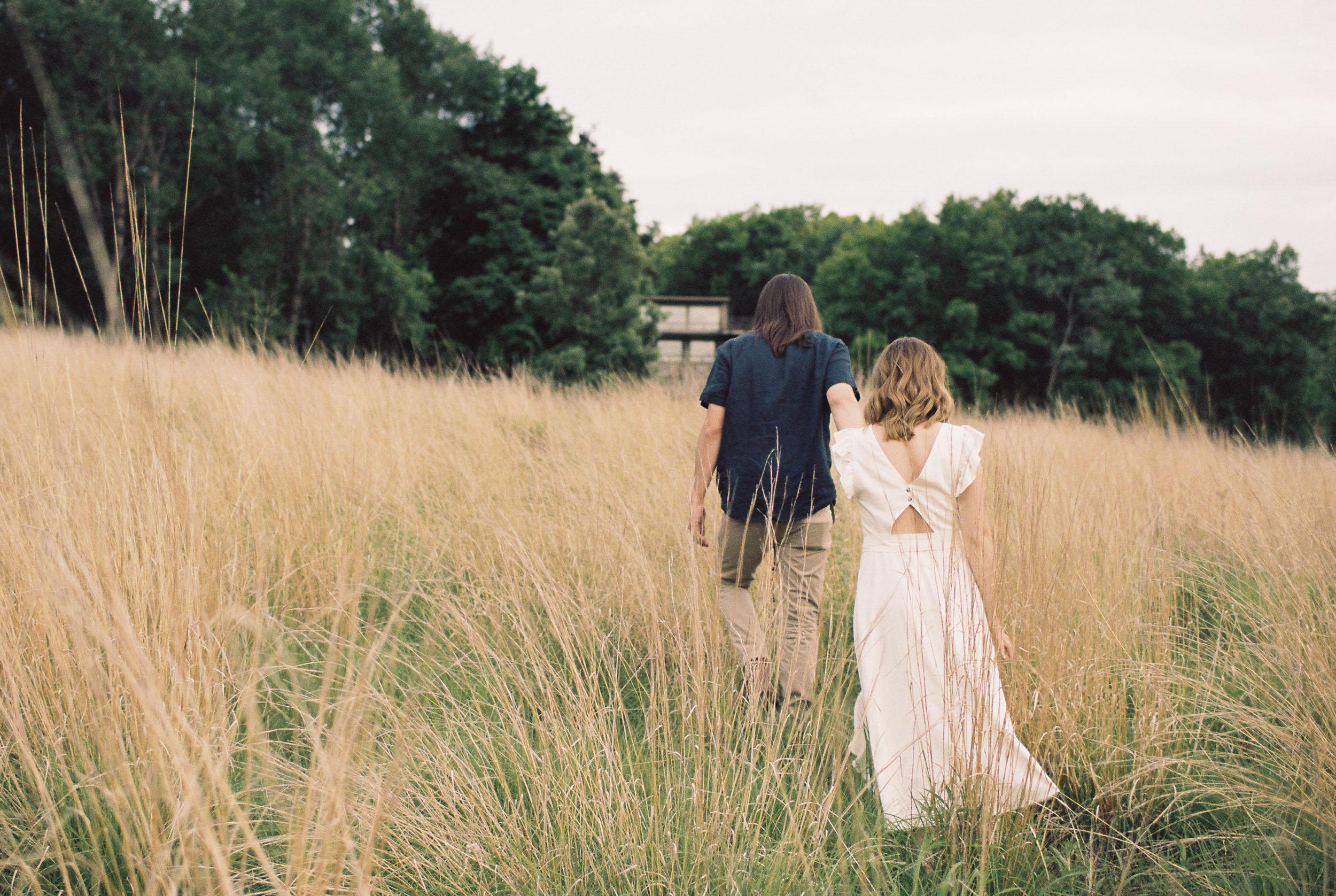 Man leading his fiancé through a field
