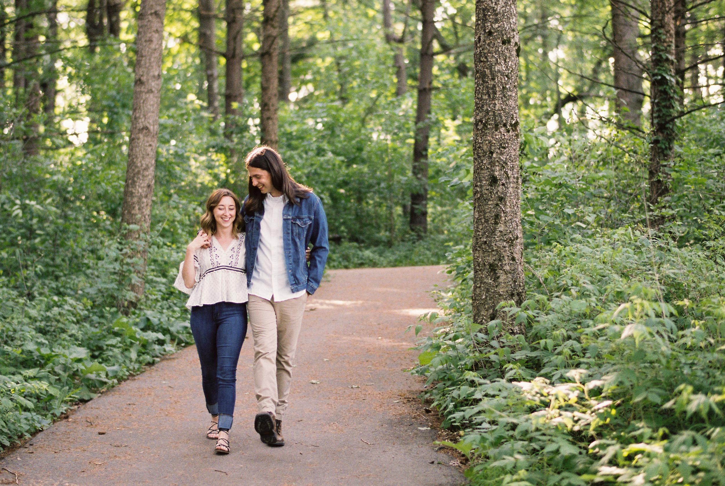 Engaged couple walking through the woods
