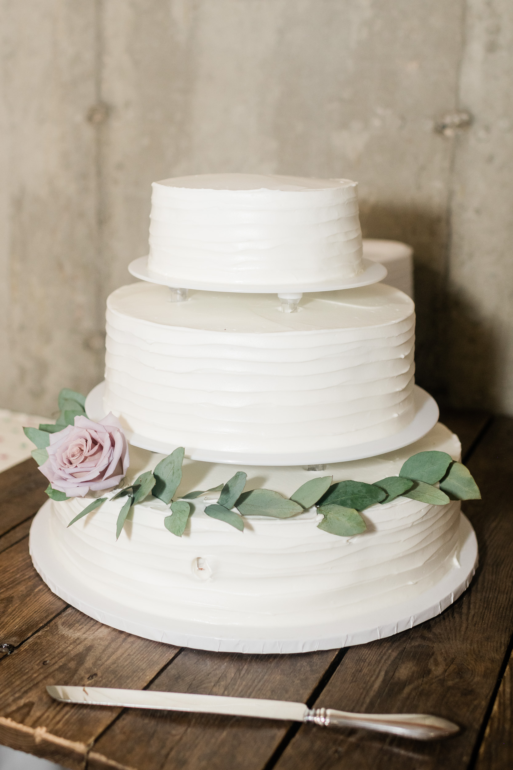 Wedding cake with white frosting and greenery