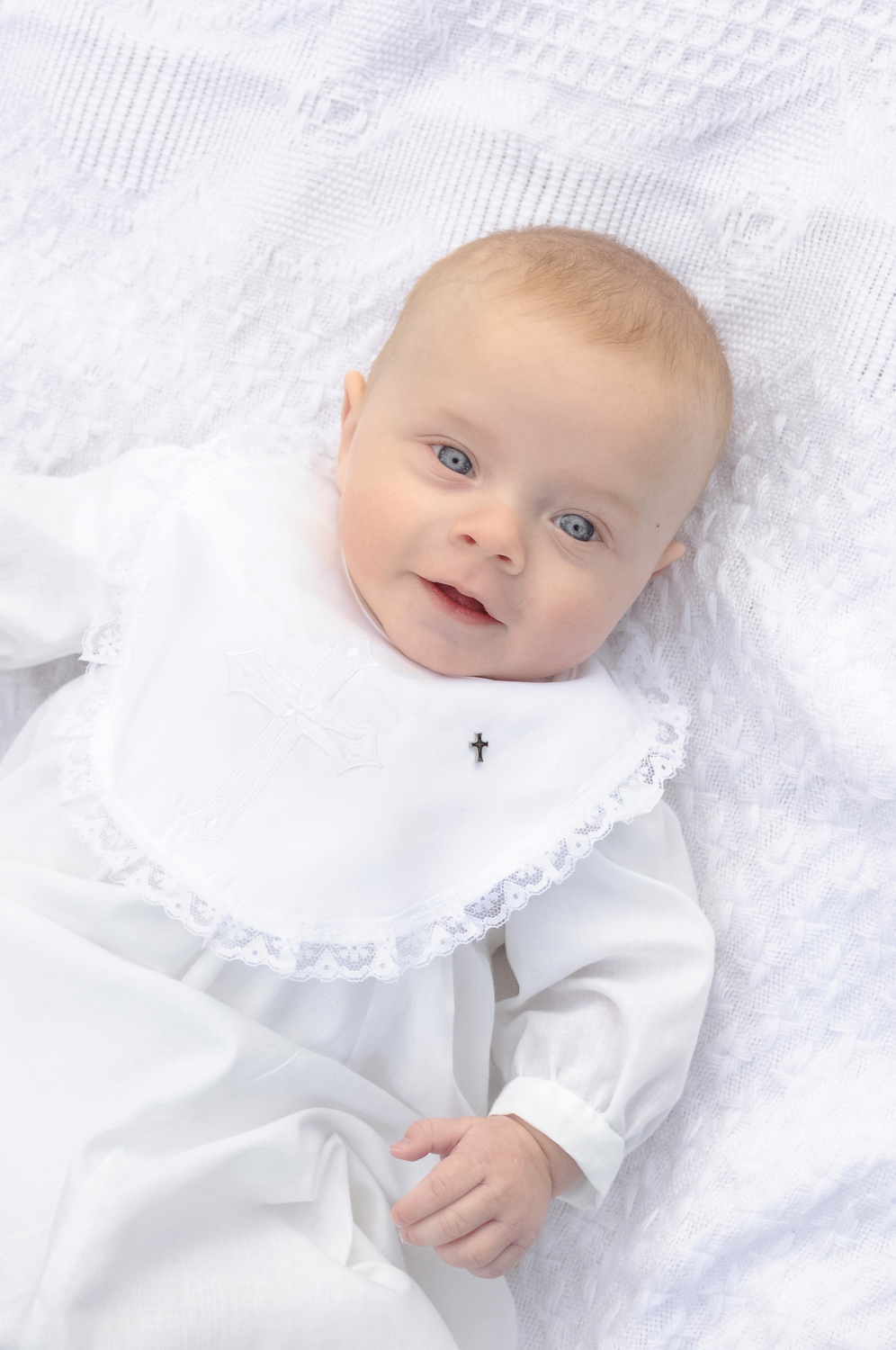 st-louis-baby-photography-boy-in-white-baptisim-gown-on-white-blanket.jpg
