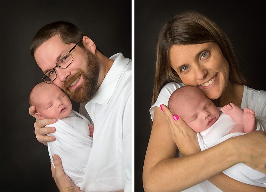 st-louis-newborn-photographer-mom-and-dad-in-white-holing-baby-boy-on-black-backdrop.jpg