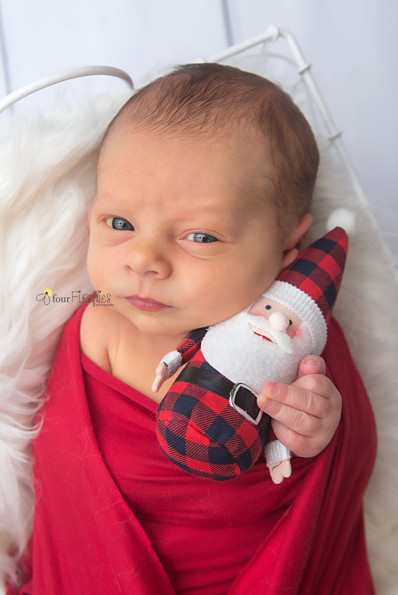 st-louis-newborn-photographer-christmas-baby-awake-holding-buffalo-plaid-stuffed-santa.jpg