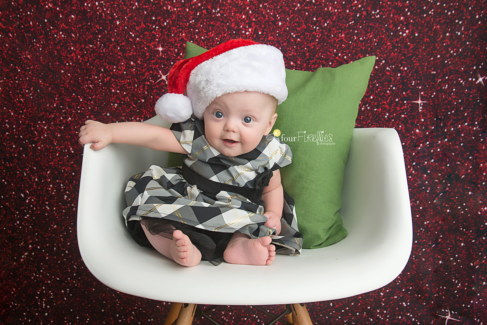 st-louis-baby-photographer-christmas-baby-in-plaid-dress-and-santa-hat-on-white-chair-with-green-pillow-and-red-glitter-backdrop.jpg