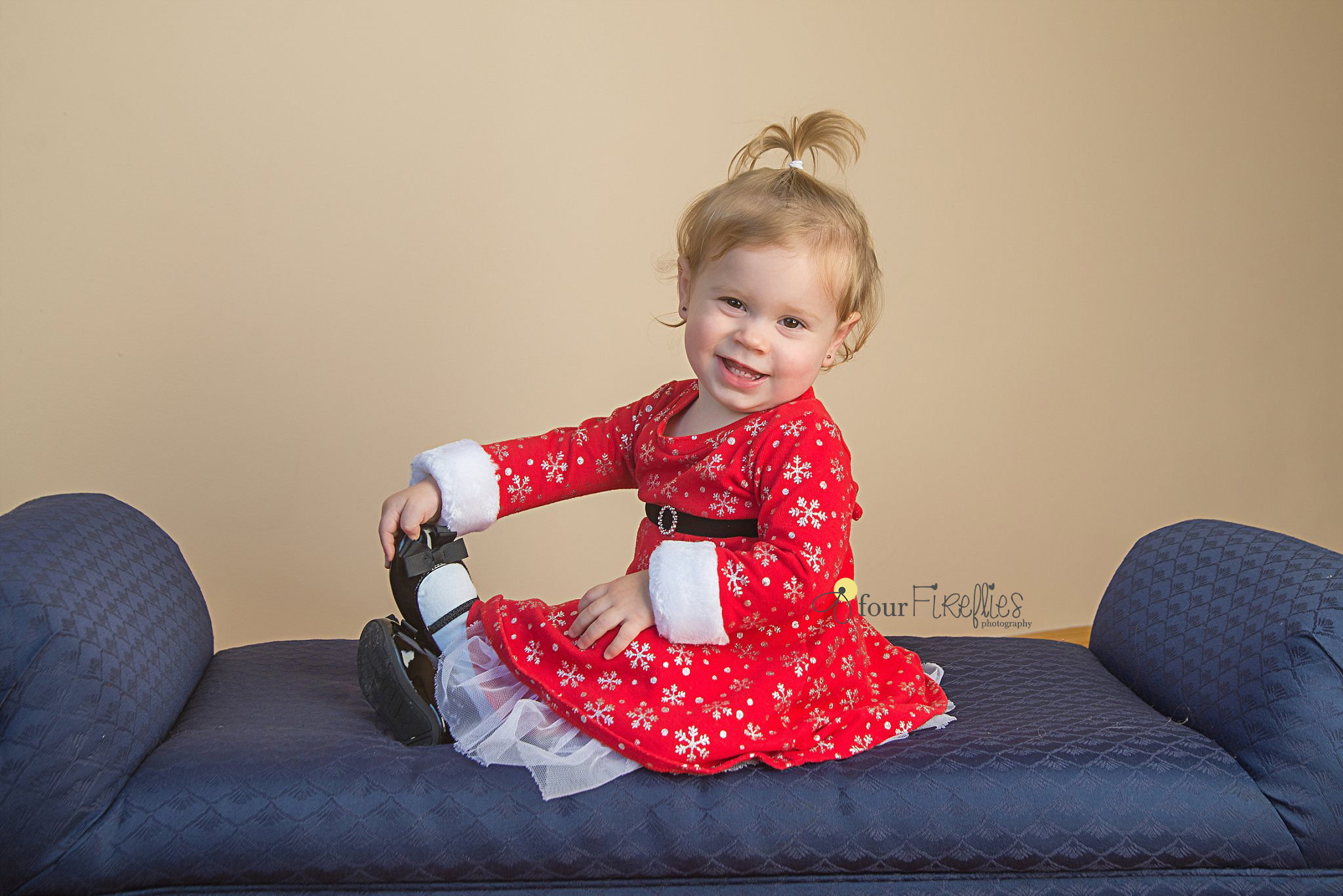 st-louis-photography-studio-girl-in-christmas-dress-holding-feet-on-blue-couch.jpg