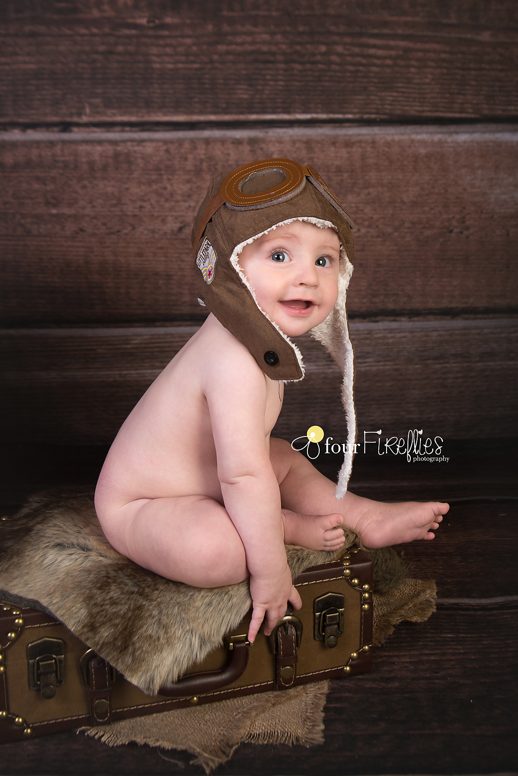 st-louis-photography-studio-6-month-milestone-session-boy-bare-bum-on-suitcase-with-avaitor-hat-and-wood-backdrop.jpg