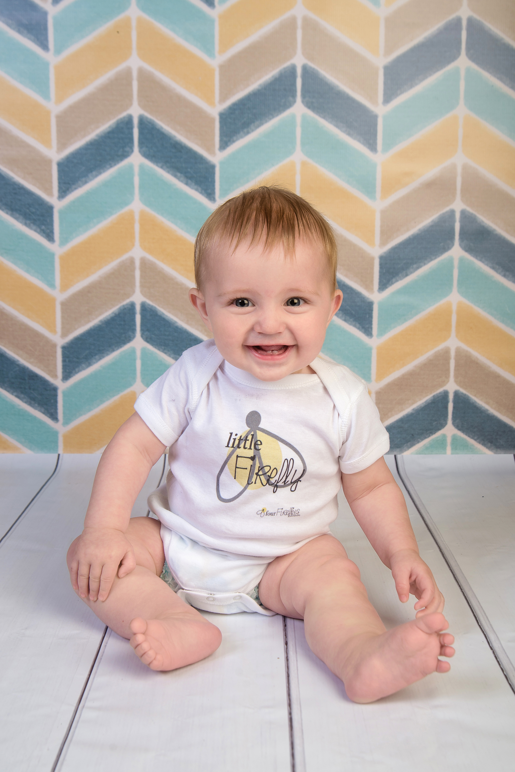 st-louis-photography-studio-six-month-milestone-session-boy-on-yellow-and-blue-weaing-four-fireflies-photography-onsie.jpg