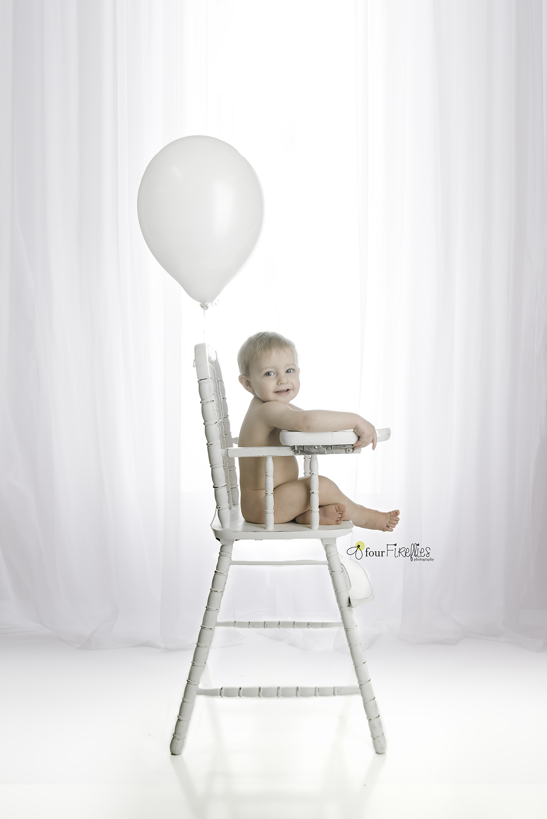 st-louis-photography-studio-first-birthday-baby-boy-in-high-chair-with-balloon-all-white-simple.jpg