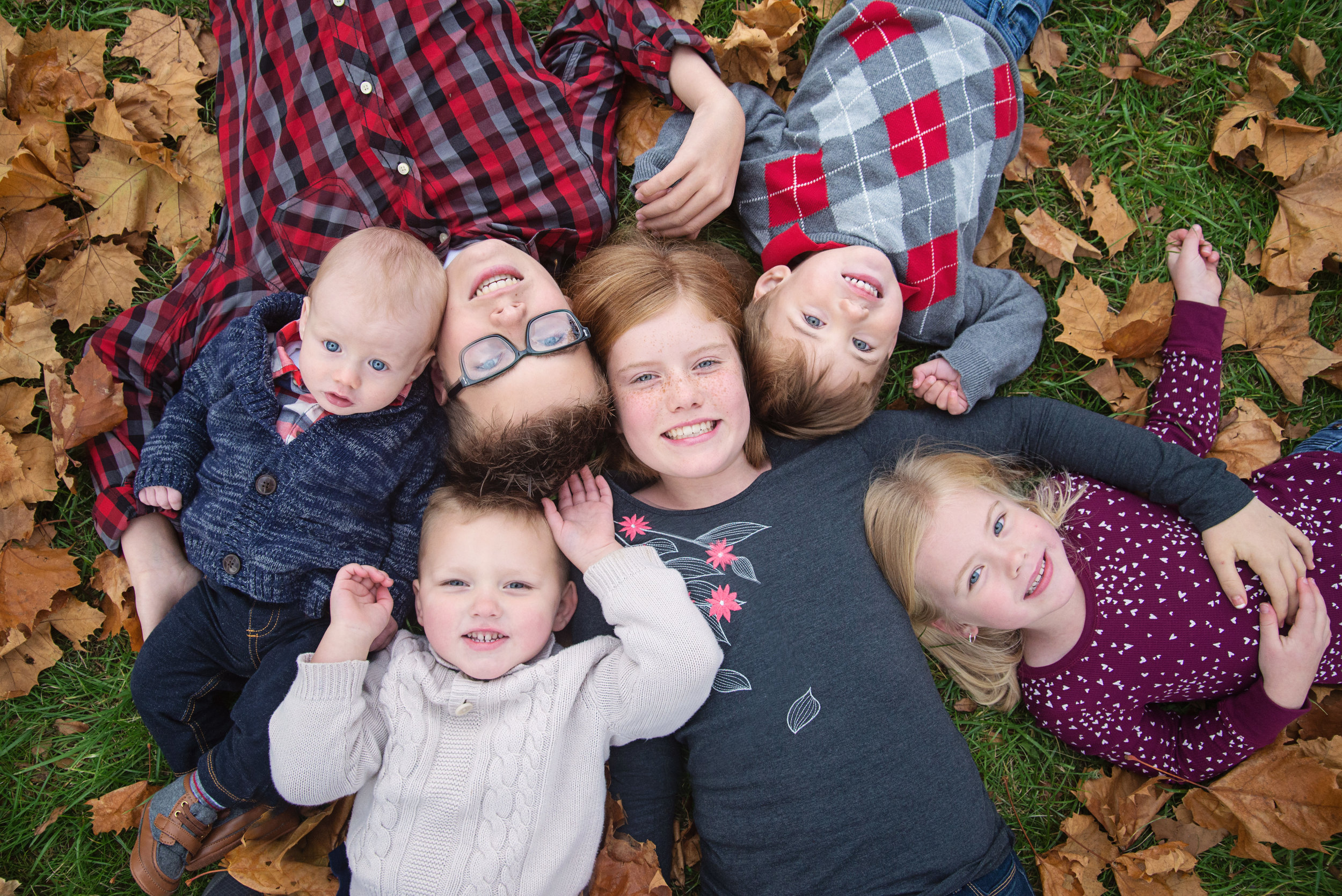 st-louis-family-photographer-six-kids-laying-in-leaves-looking-up-with-heads-together.jpg