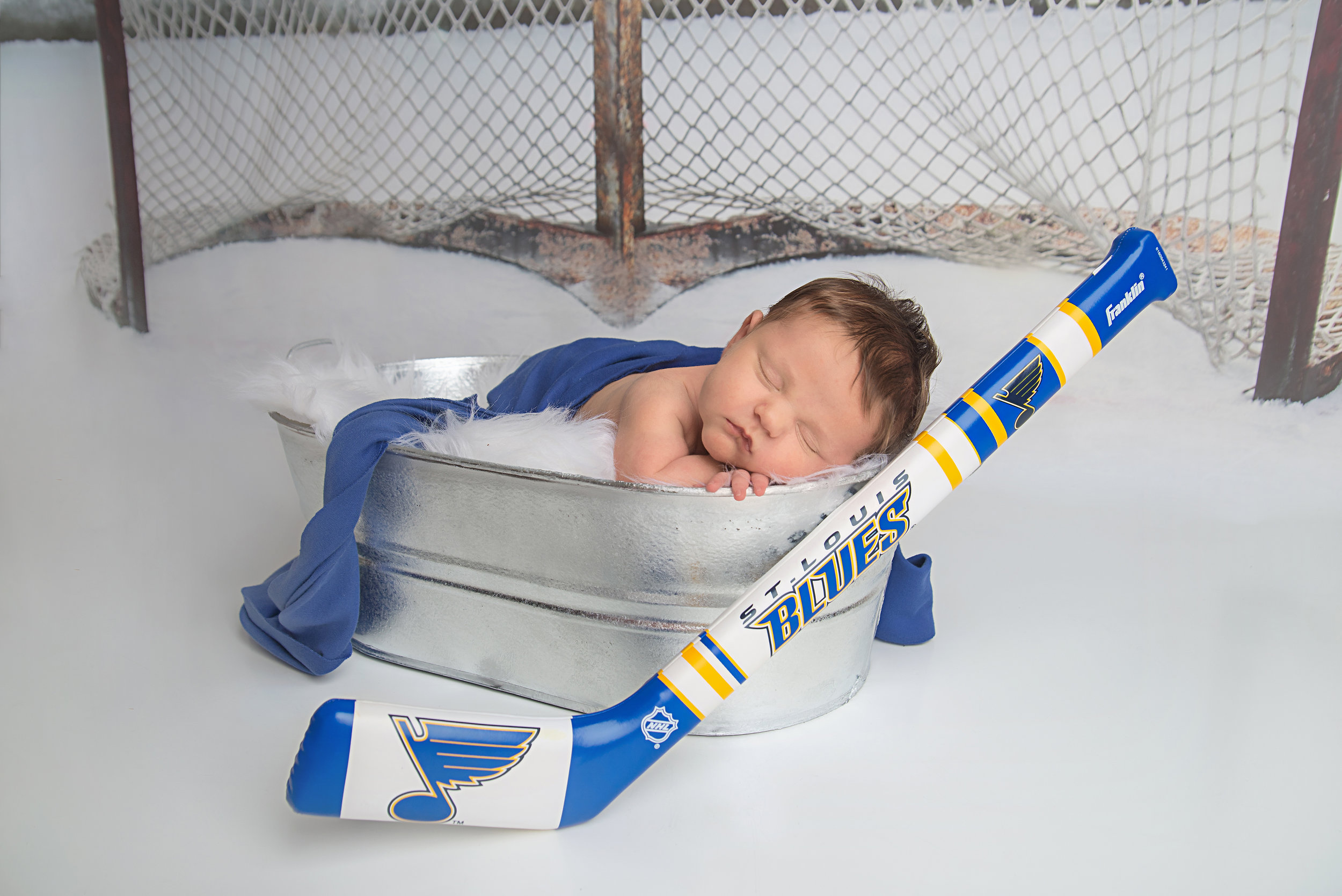 st-louis-newborn-photographer-baby-boy-with-st-louis-blues-hockey-and-hockey-net-backdrop.jpg
