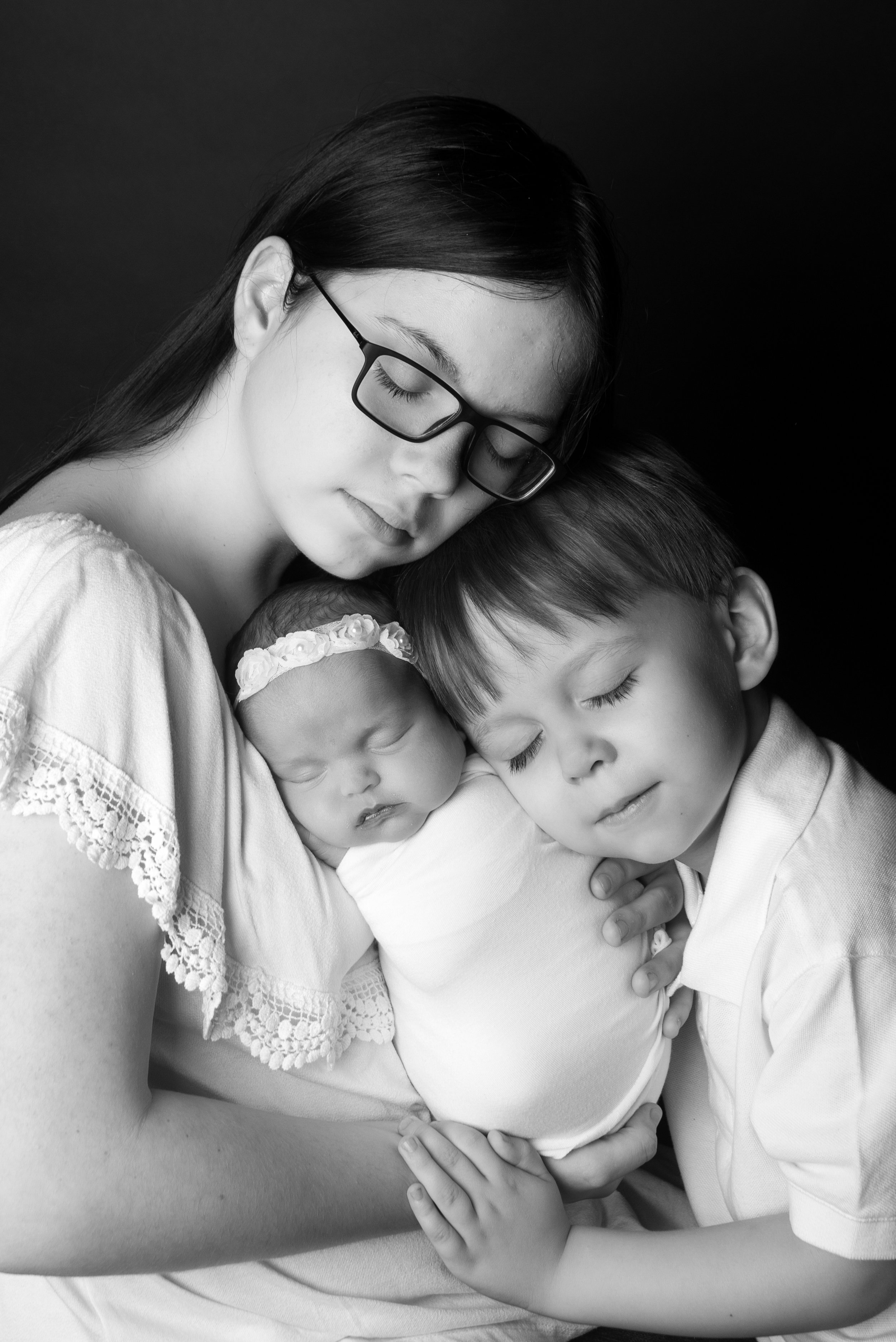 st-louis-newborn-photographer-black-and-white-picture-of-baby-girl-with-big-brother-and-sister-eye-closed.jpg